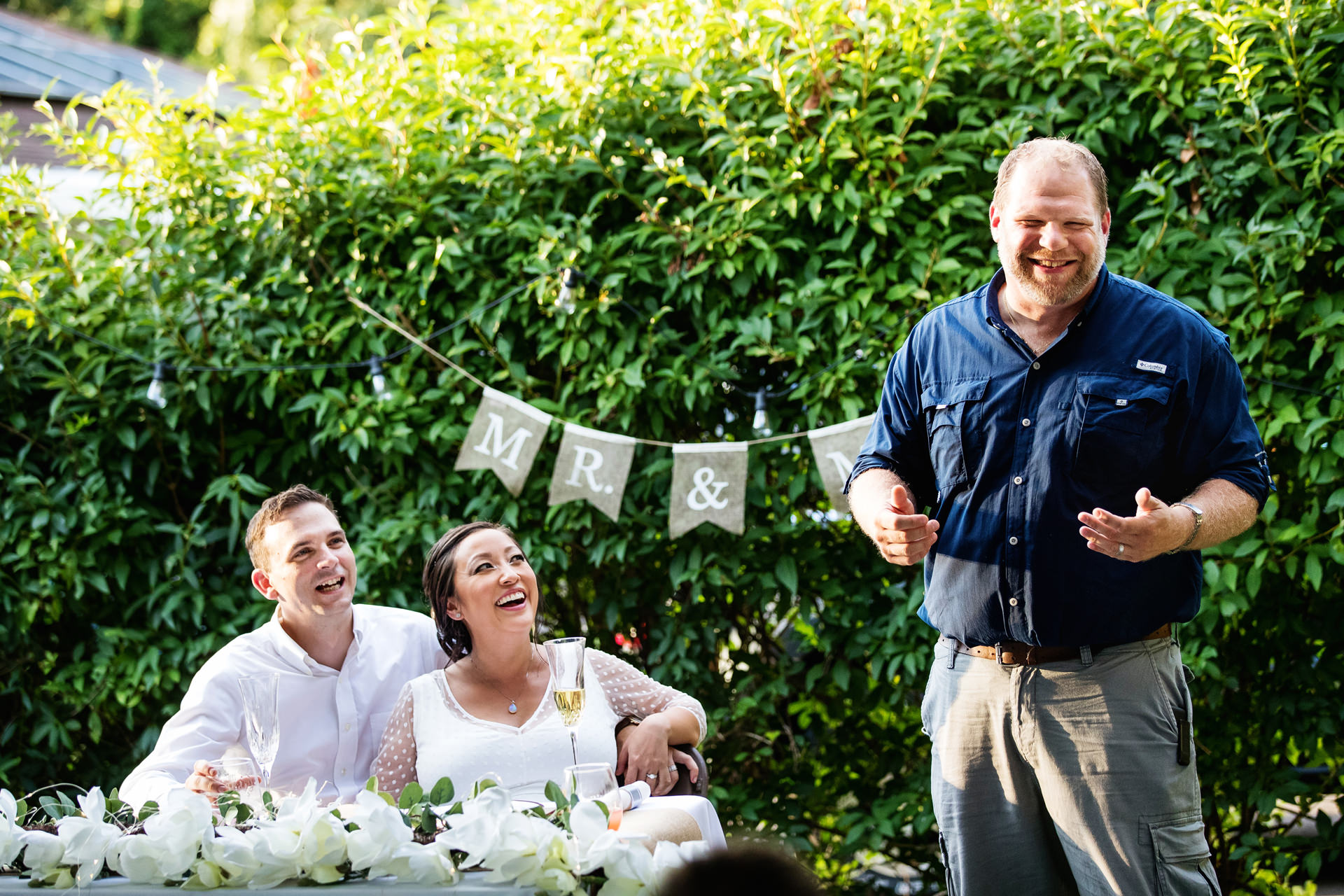 Elopement Wedding Images | The bride and groom erupt in laughter during a toast at their backyard wedding
