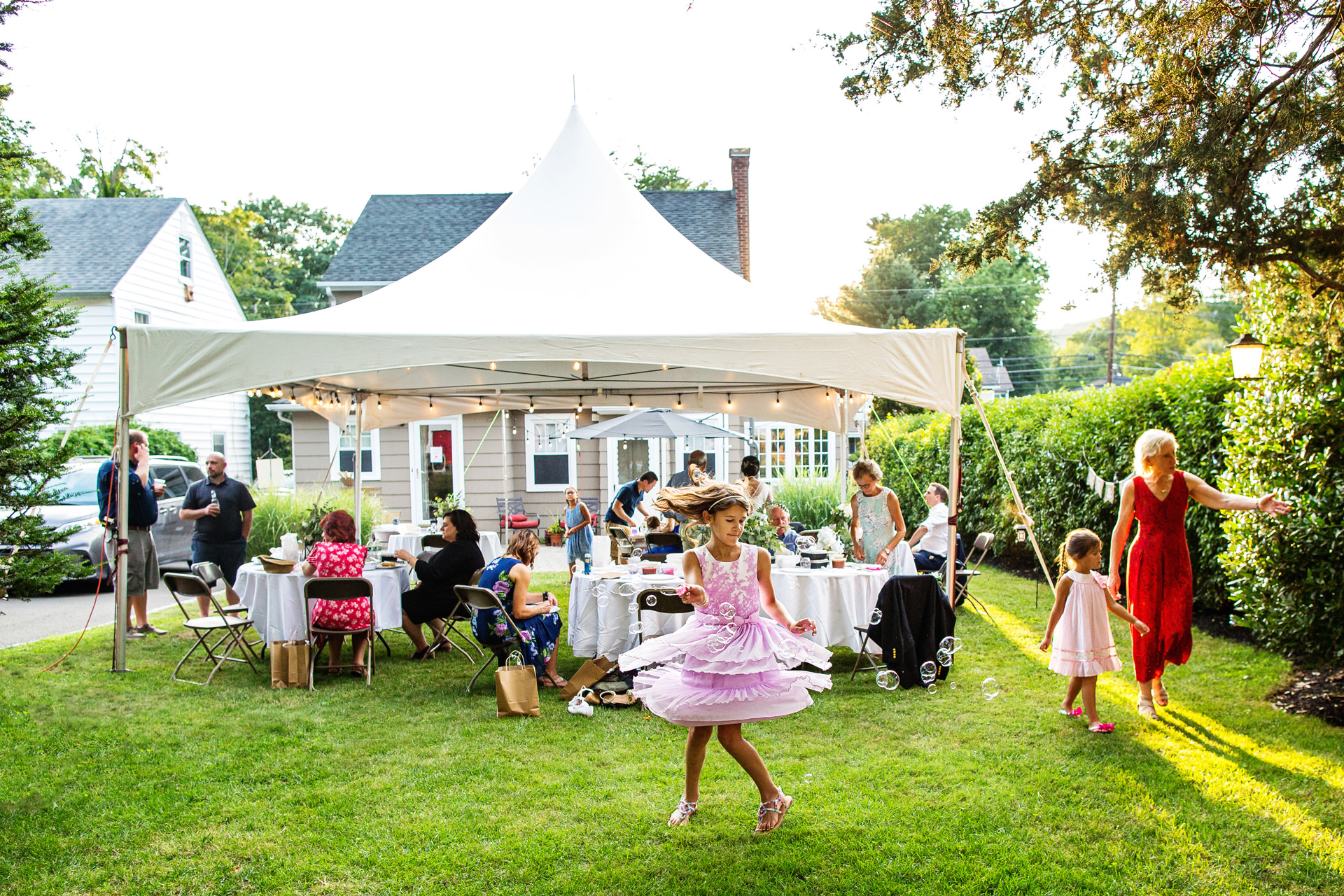 A Micro Wedding and Elopement in NJ | A niece spins with bubbles as the sun sets in their New Jersey backyard