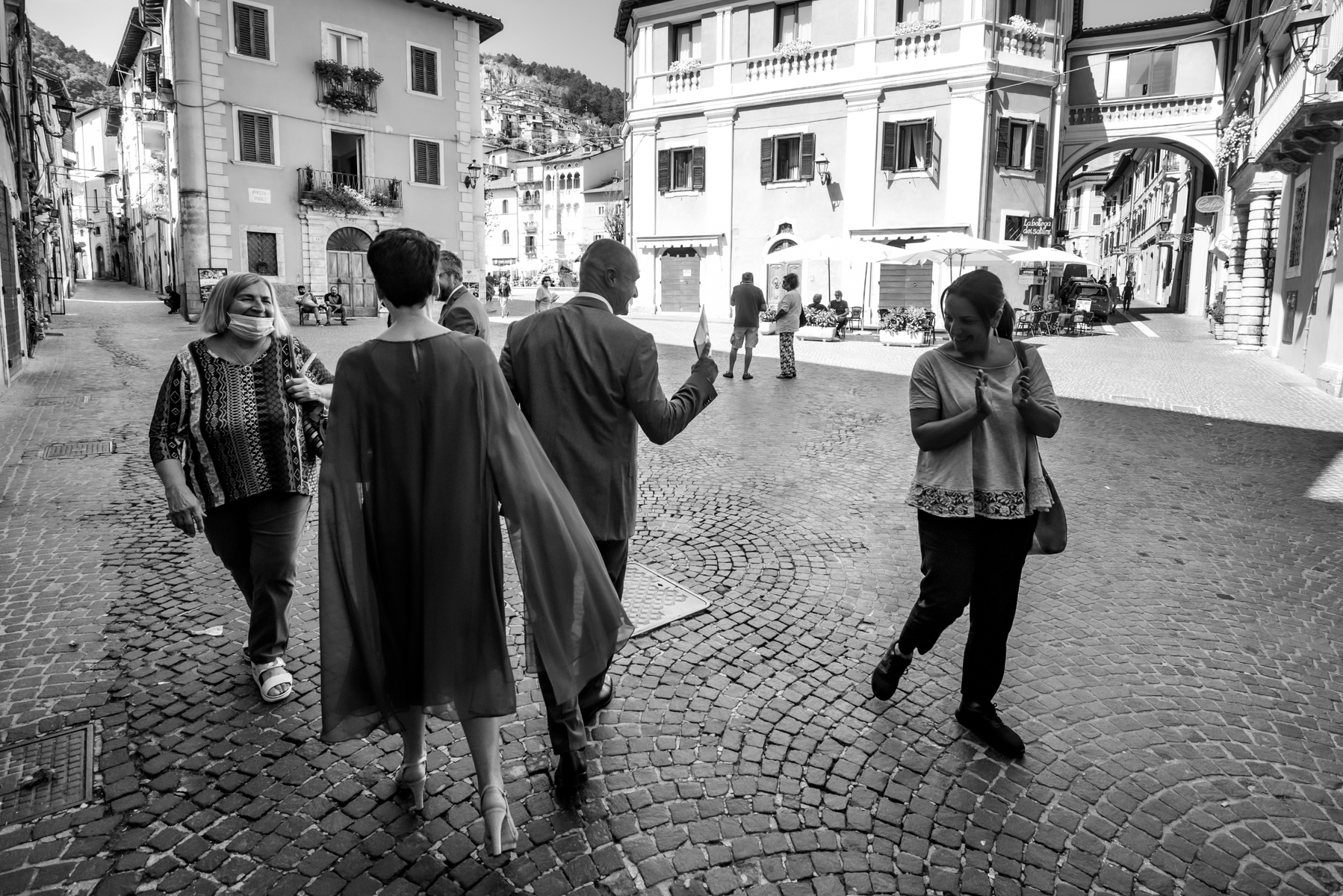 Piazza Obelisco Elopement Photography - L'Aquila - Italy | The bride and groom, with their guests in line, walk to the reception venue heading towards the central square of the town