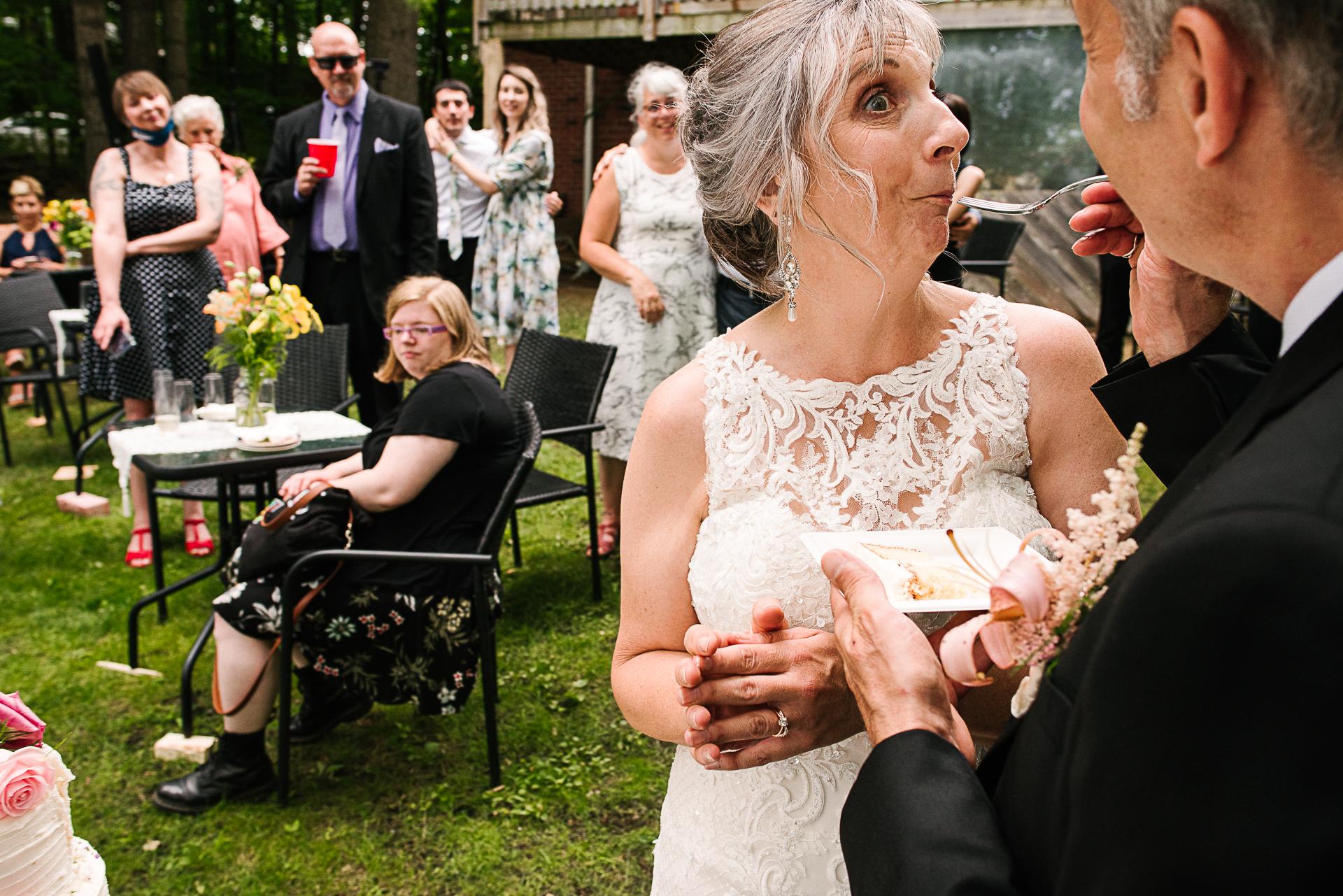Ontario Outdoor Elopement Photographer | Feeding cake during their backyard, outdoor wedding reception