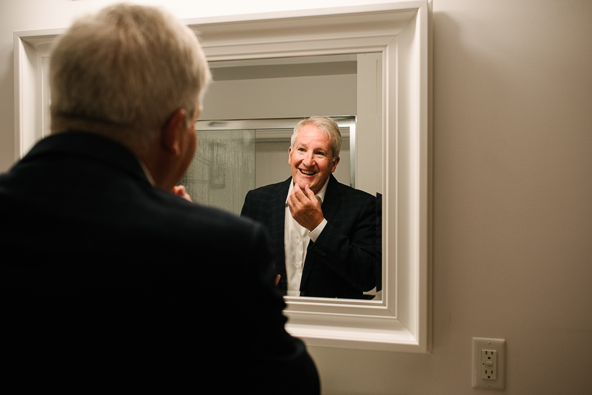 At-Home Elopement Photos - Ontario | The groom looks at himself in the mirror and smiles
