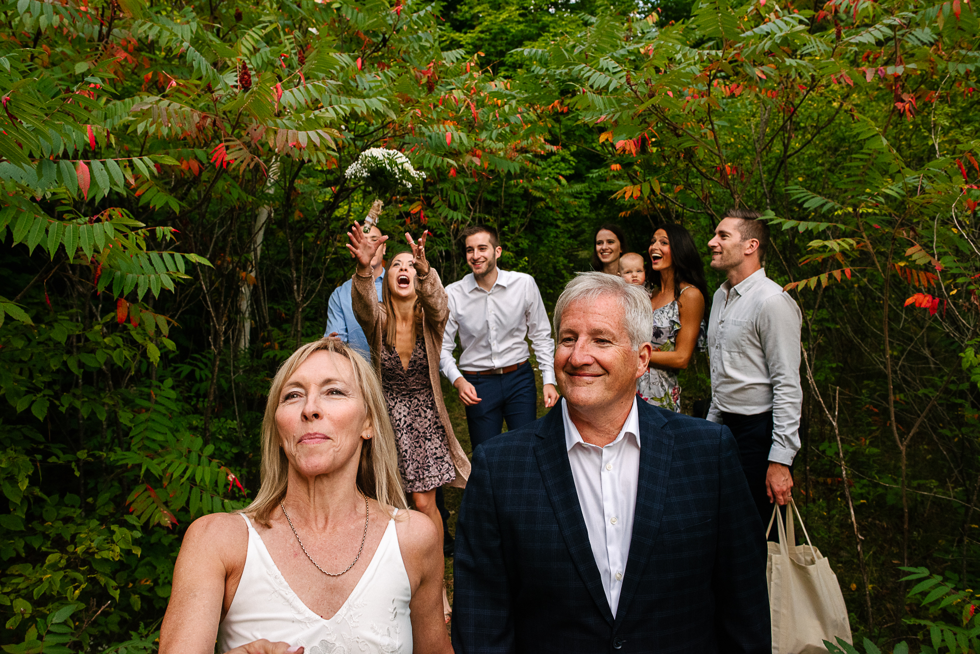 Ontario Backyard Elopement Reception Flower Toss | The bride tosses her bridal bouquet behind her, and her daughter catches