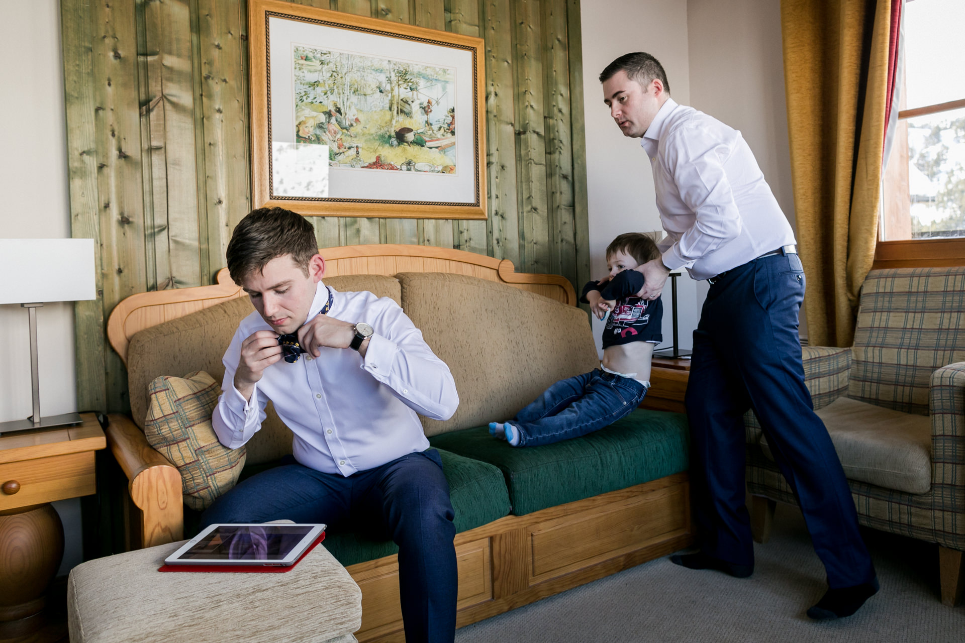 Les Arcs Elopement Picture | The groom checks out an online tutorial for how to tie a bow tie