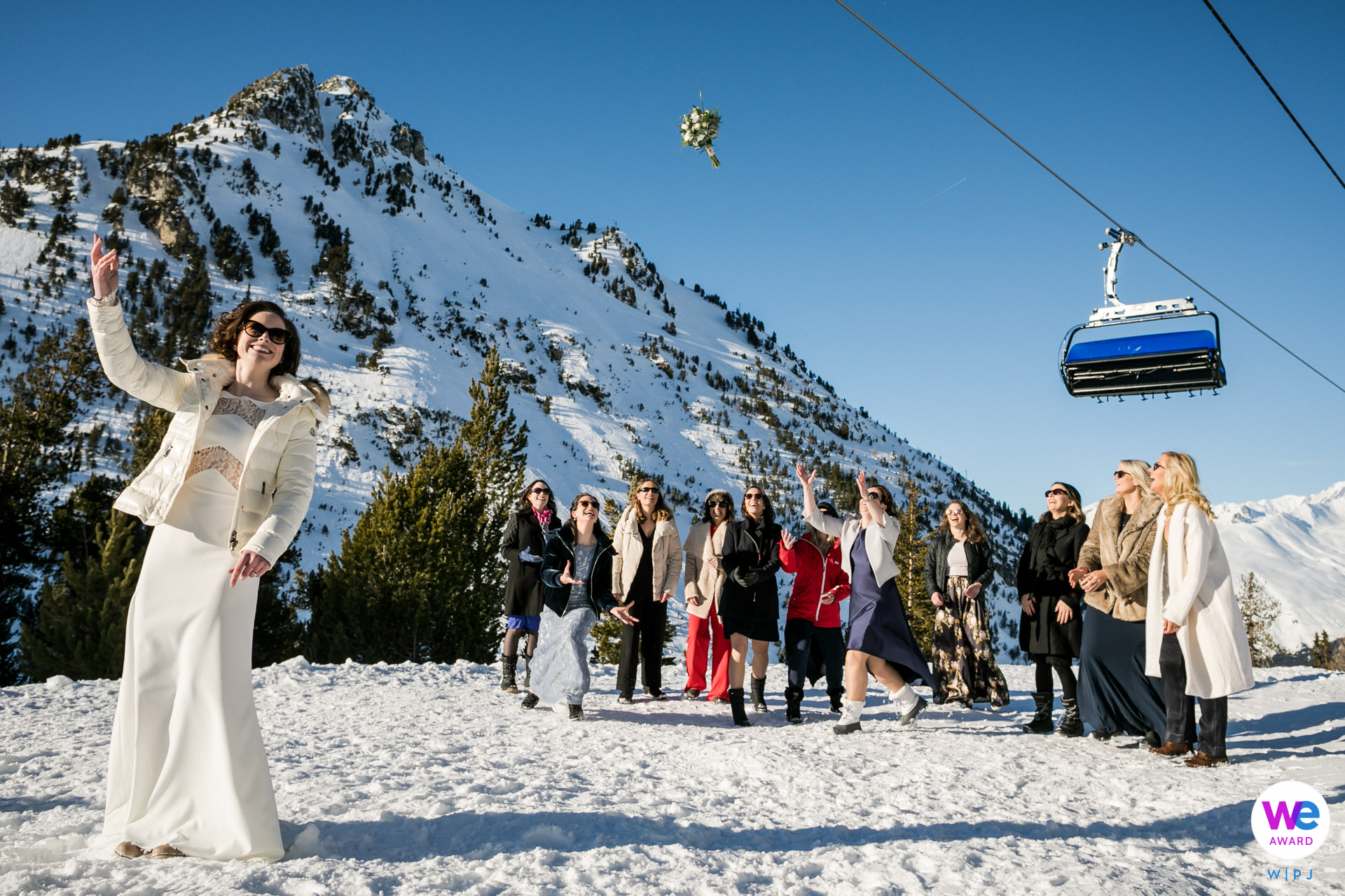Alpine Wedding Photo - France Ski Resort Elopements | The bride tosses her bouquet towards her friends and family on the ski slopes