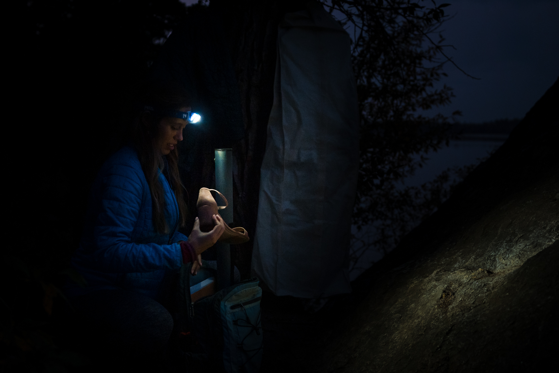 Elopement Photos in Grand Teton National Park | The bride starting to unpack her wedding dress in the dark