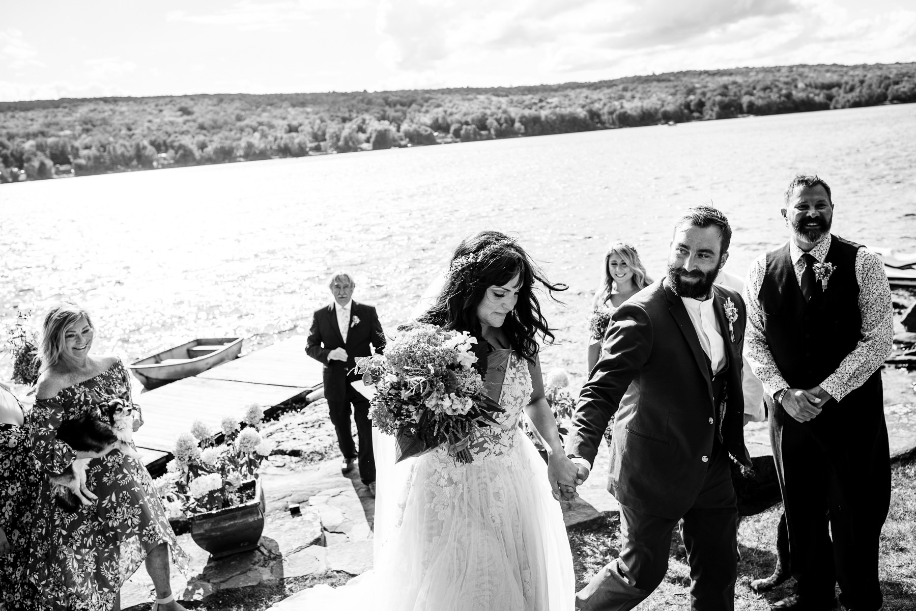 Adirondacks NY Lake Elopement Ceremony Foto | De bruid en bruidegom verlaten hun huwelijksceremonie aan het meer