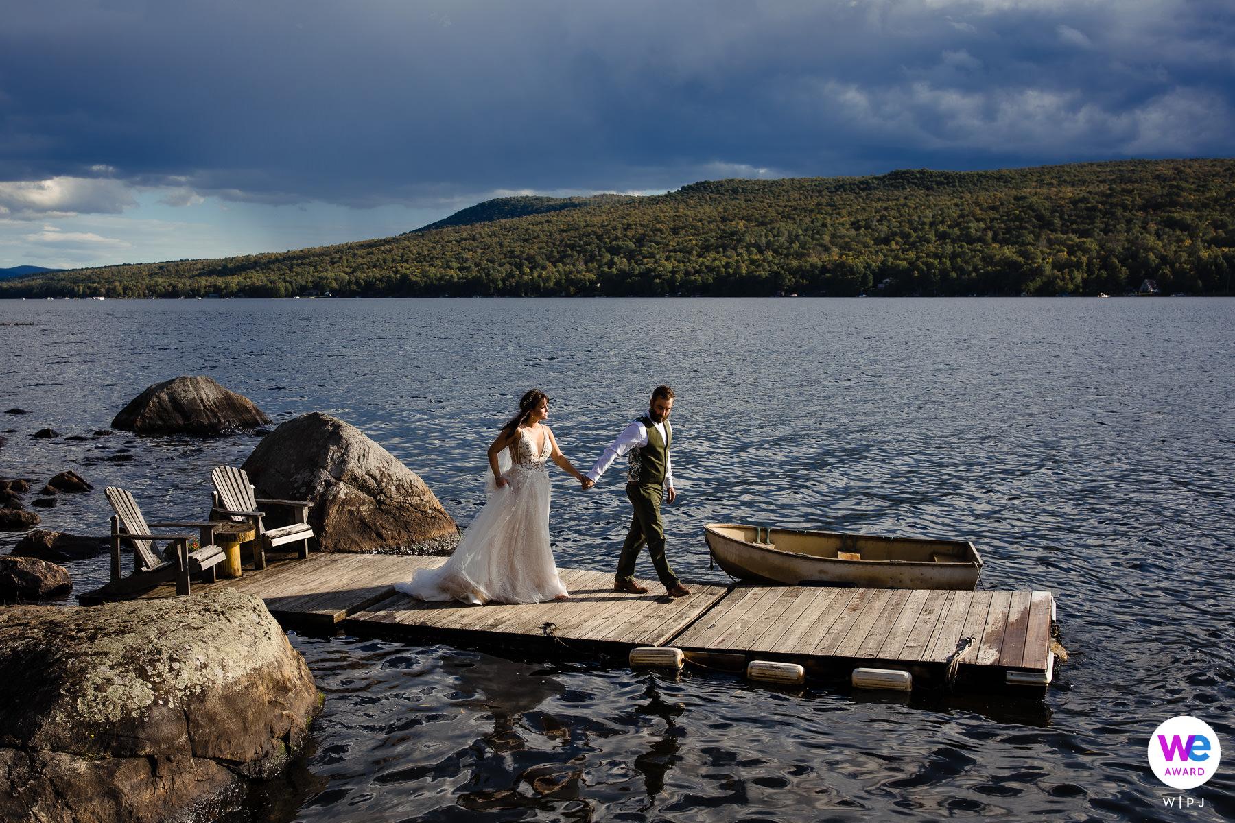 Photographes de mariage à Chateaugay, NY | Le couple voulait prendre des photos sur le quai et le marié aidait la mariée à marcher jusqu'au bout
