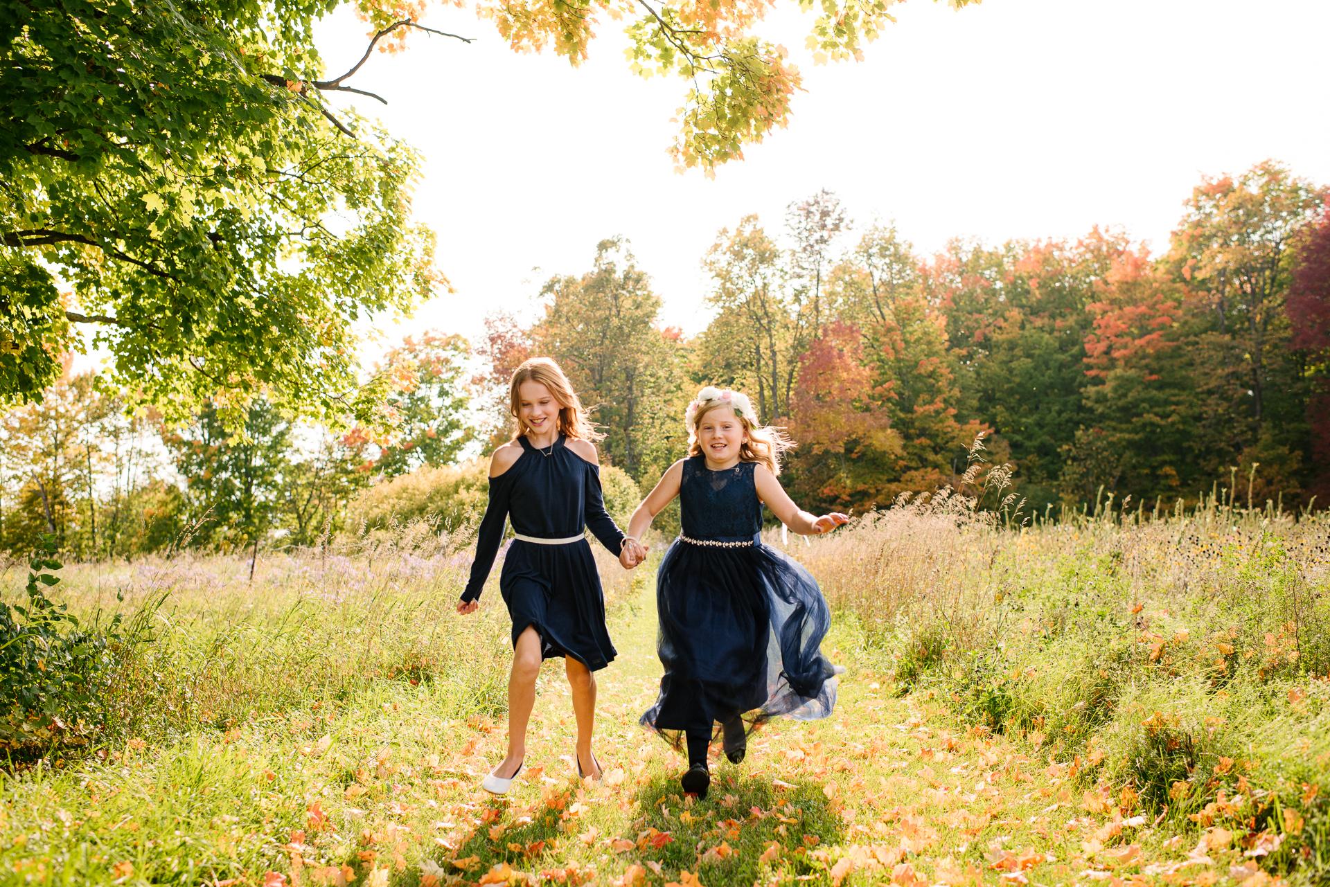 Ontario Hochzeitsfotograf | Die Blumenmädchen halten sich an den Händen, als sie zur Zeremonie springen