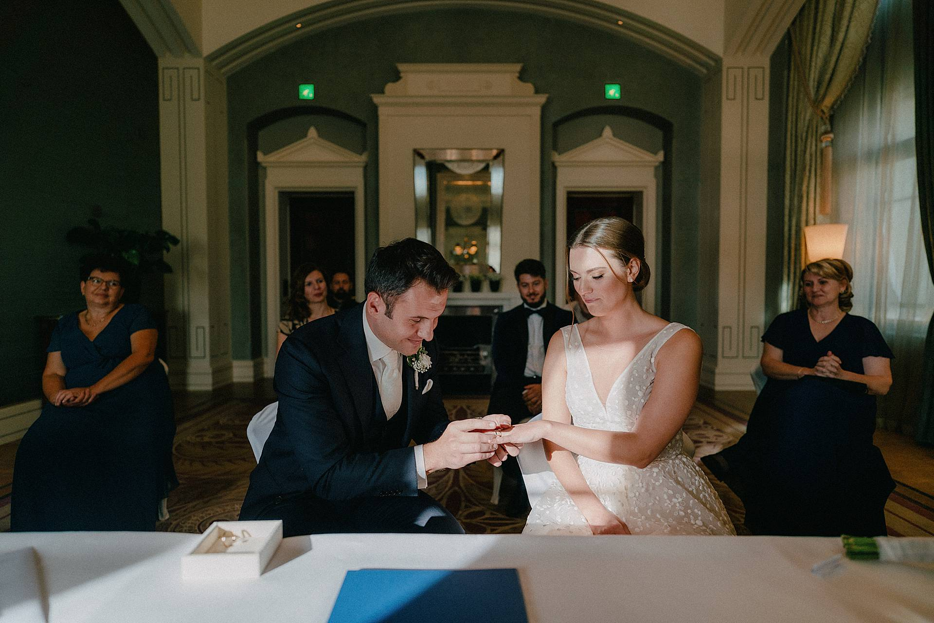 Zurich Wedding Photographer - Dolder Grand | The groom places a wedding ring on the brides finger