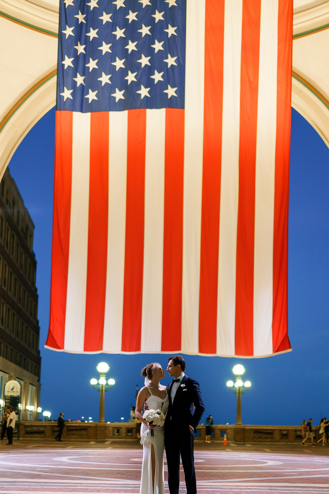 Boston Waterfront Harbor Hotel Weddings | The sun sets on their wedding day under a huge USA flag