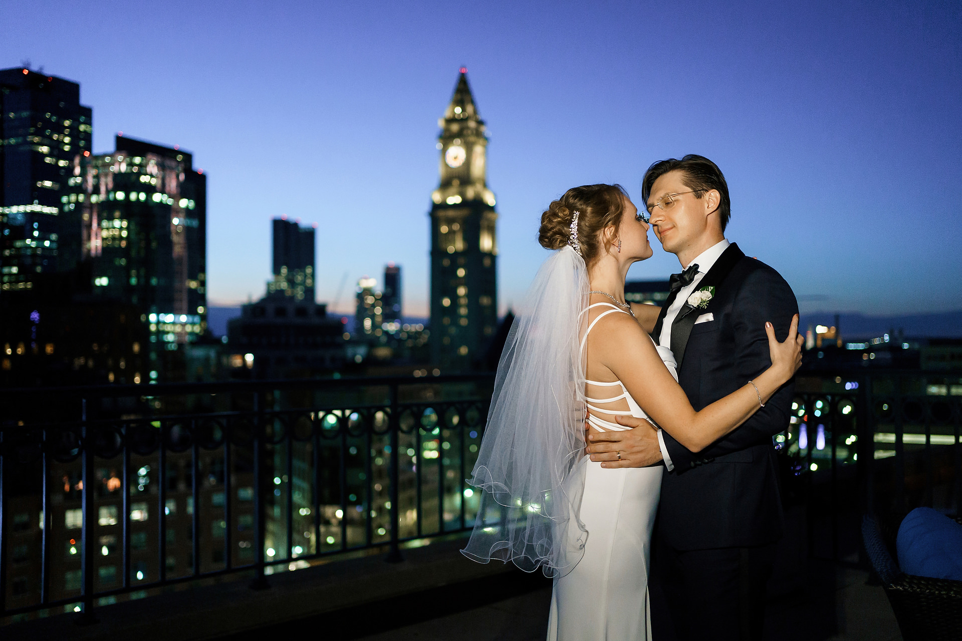 A Boston Harbor Hotel Wedding Portrait | the skyline is glittering in the background