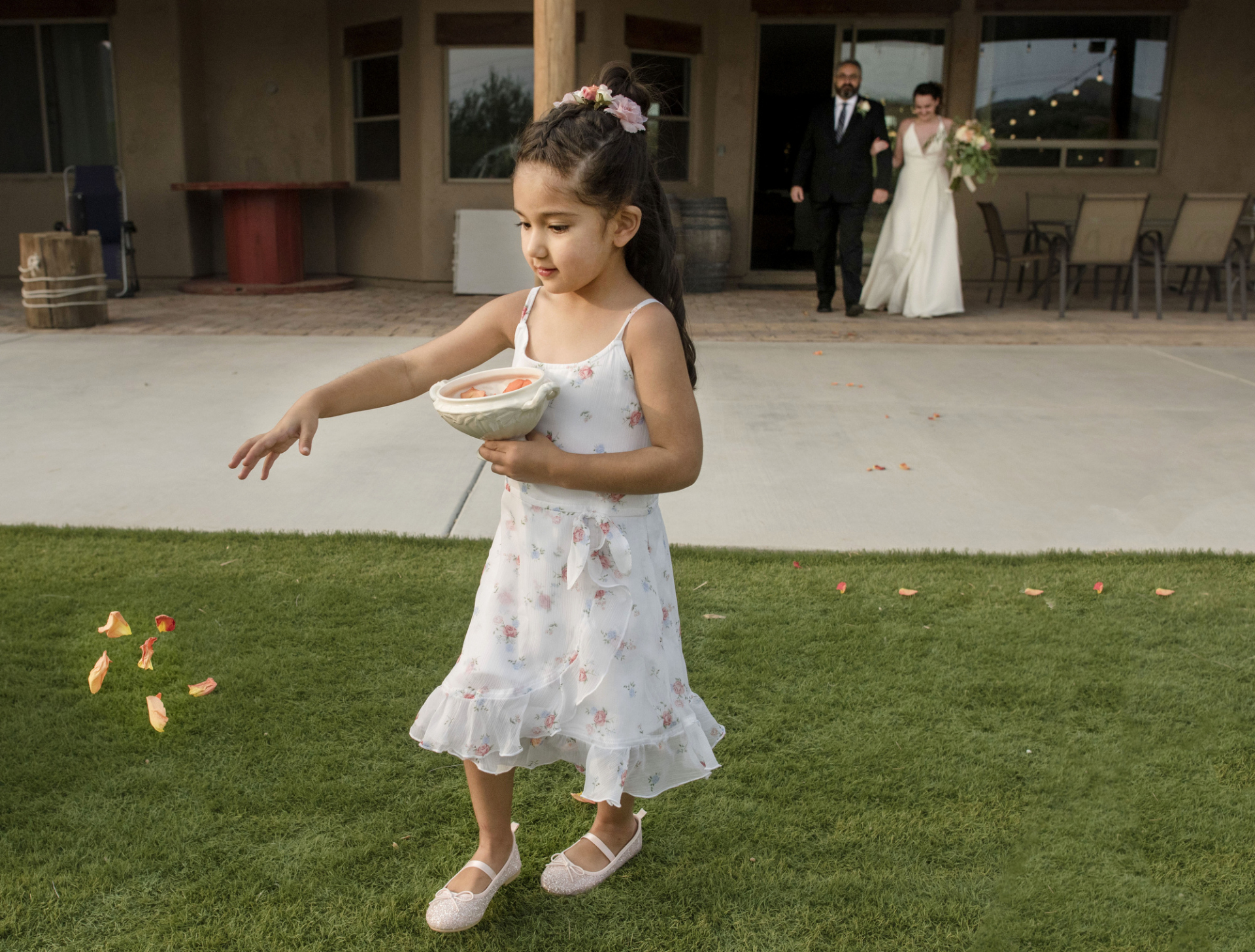 New River, Arizona Elopement Photographer | The flower girl tosses rose petals on the lawn