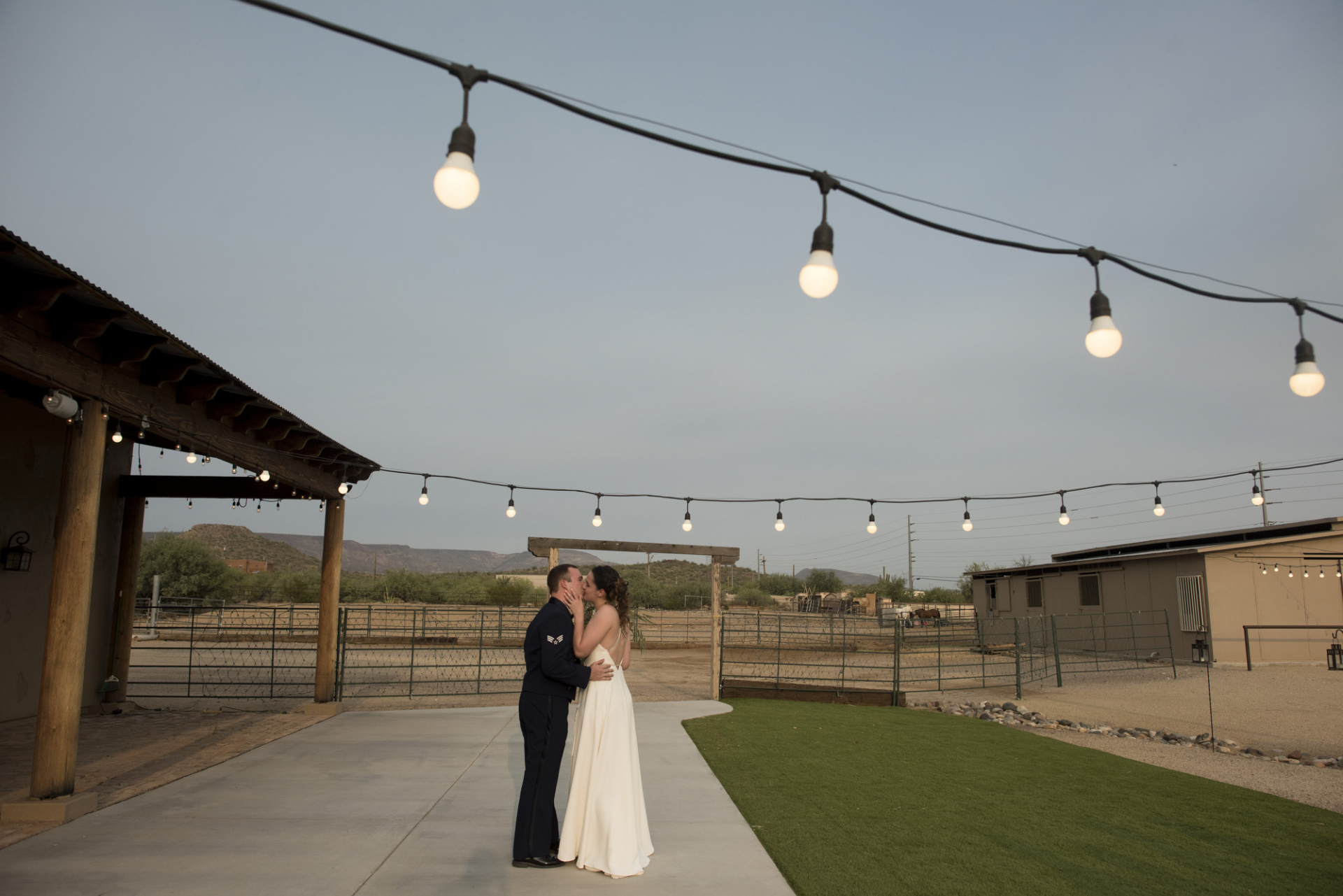 Wedding & Elopement Photographer for New River, AZ | The couple is Framed by the strings of lights that were set up for the wedding