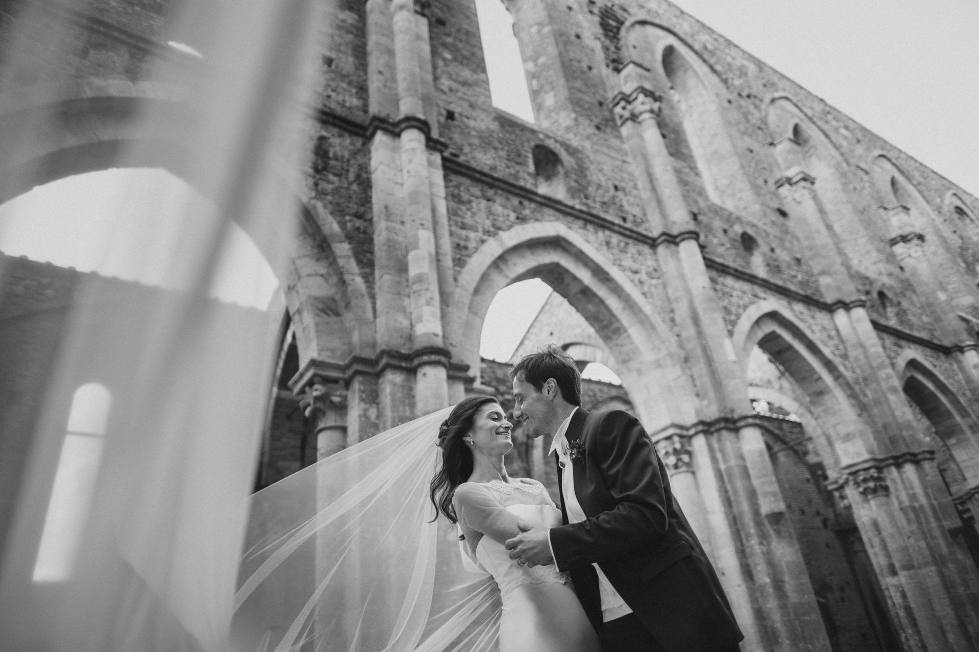 San Galgano Abbey Elopement Picture, Chiusdino - Italian Weddings   Just after sunset, the newlyweds smile at one another