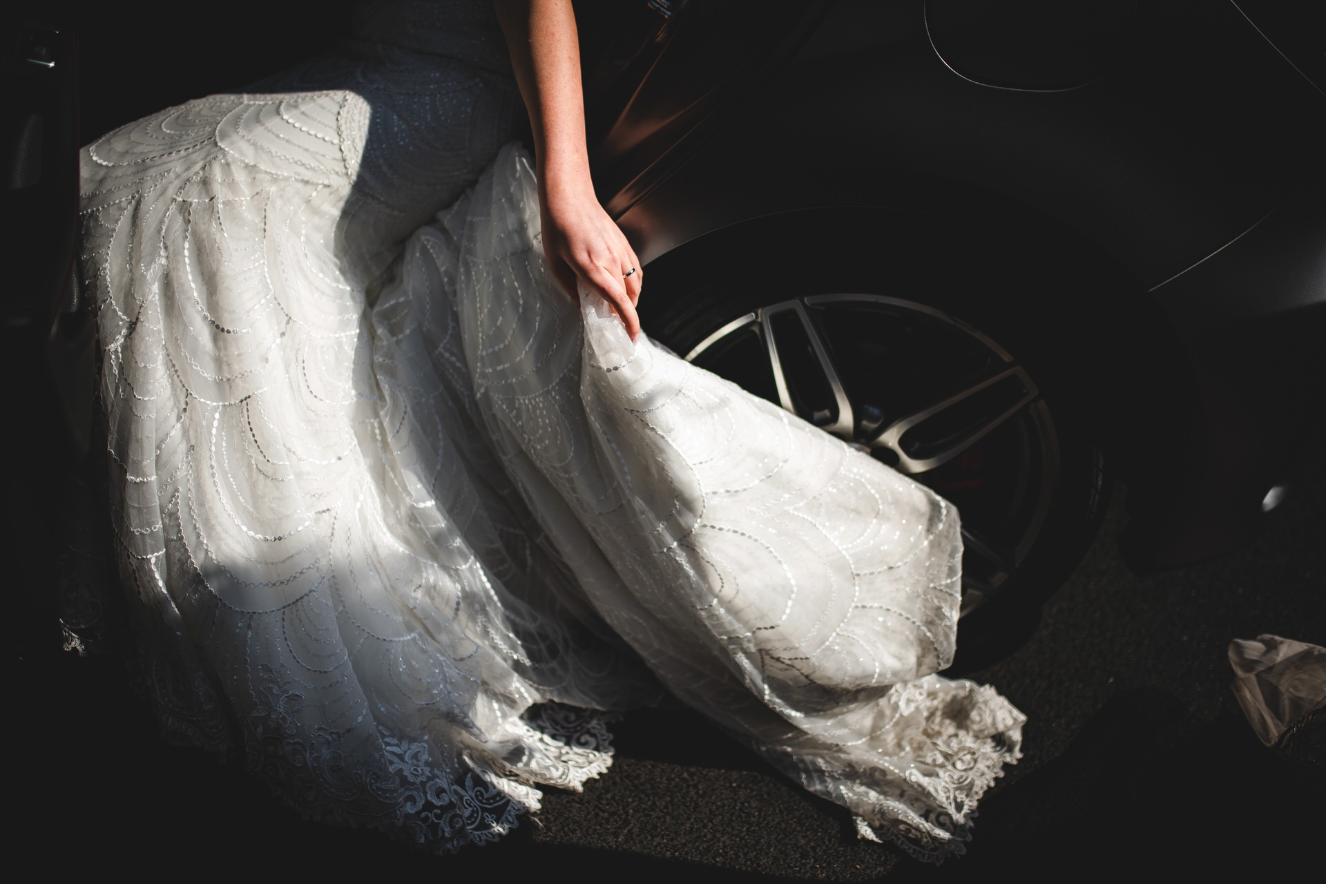 Florence Town Hall Wedding Photos | the bride carefully pulls the train of her lace gown away from the car tire
