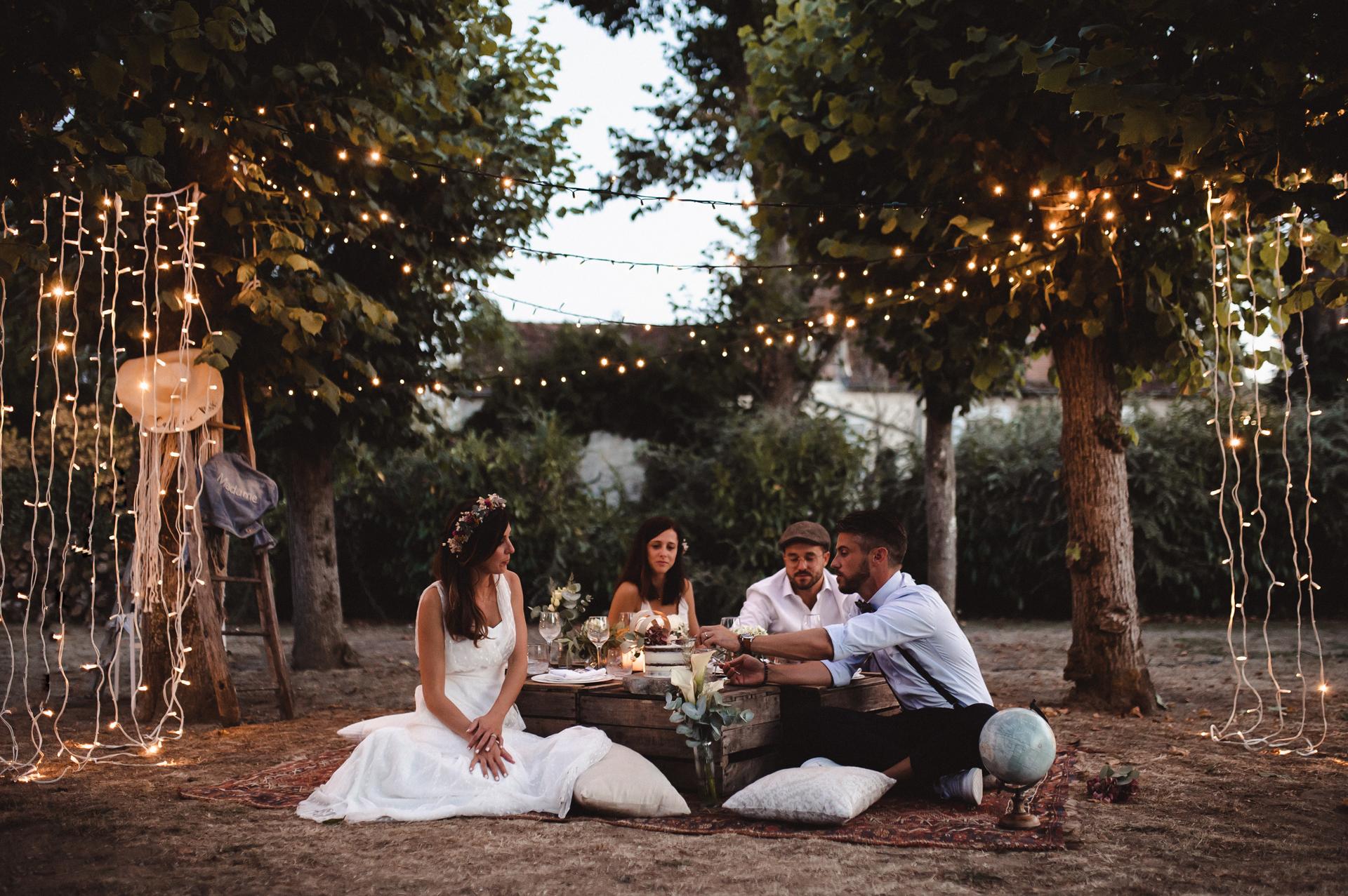 法国新娘和新郎结婚照| 新娘和新郎坐着童话般的灯光,头顶上野餐