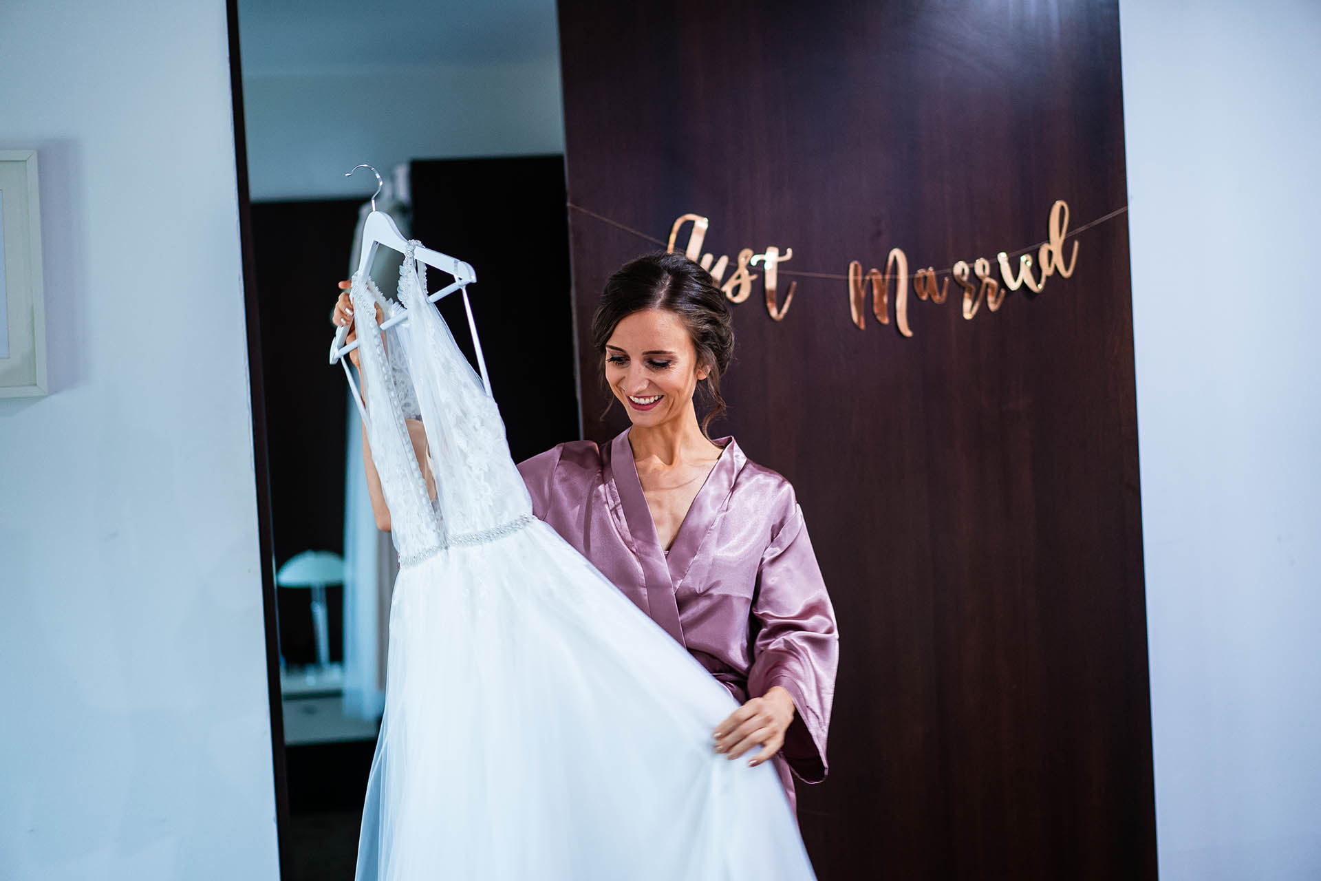 Villa Ekaterina, Vakarel, Bulgaria Wedding Photography | The bride smiles while looking at her wedding gown