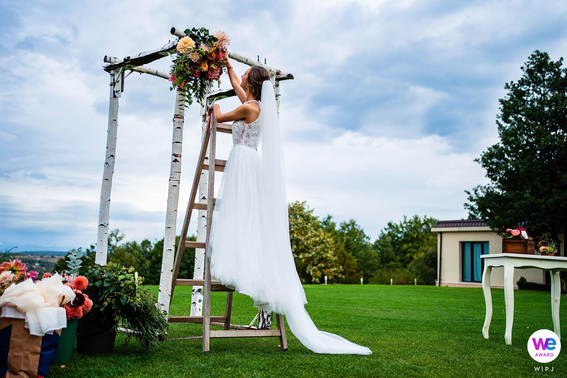 Fotografia di matrimonio da Villa Ekaterina a Vakarel, Bulgaria | la sposa lavora all'ultimo minuto per perfezionare l'arco nuziale