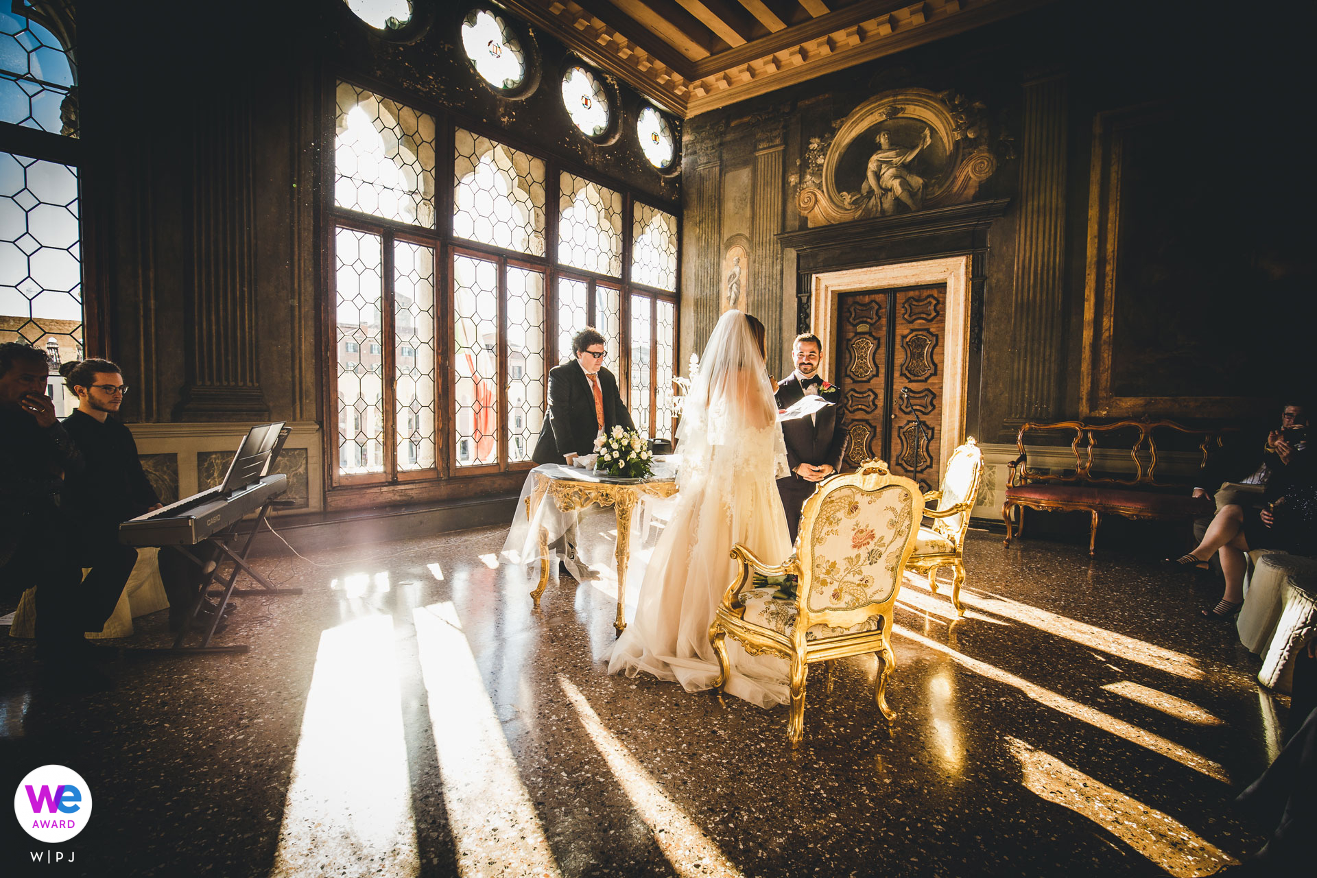 Venice Wedding Photographer at Luxurious Ca Sagredo Venue | The bride and groom take their vows in an elegant, sunlit room