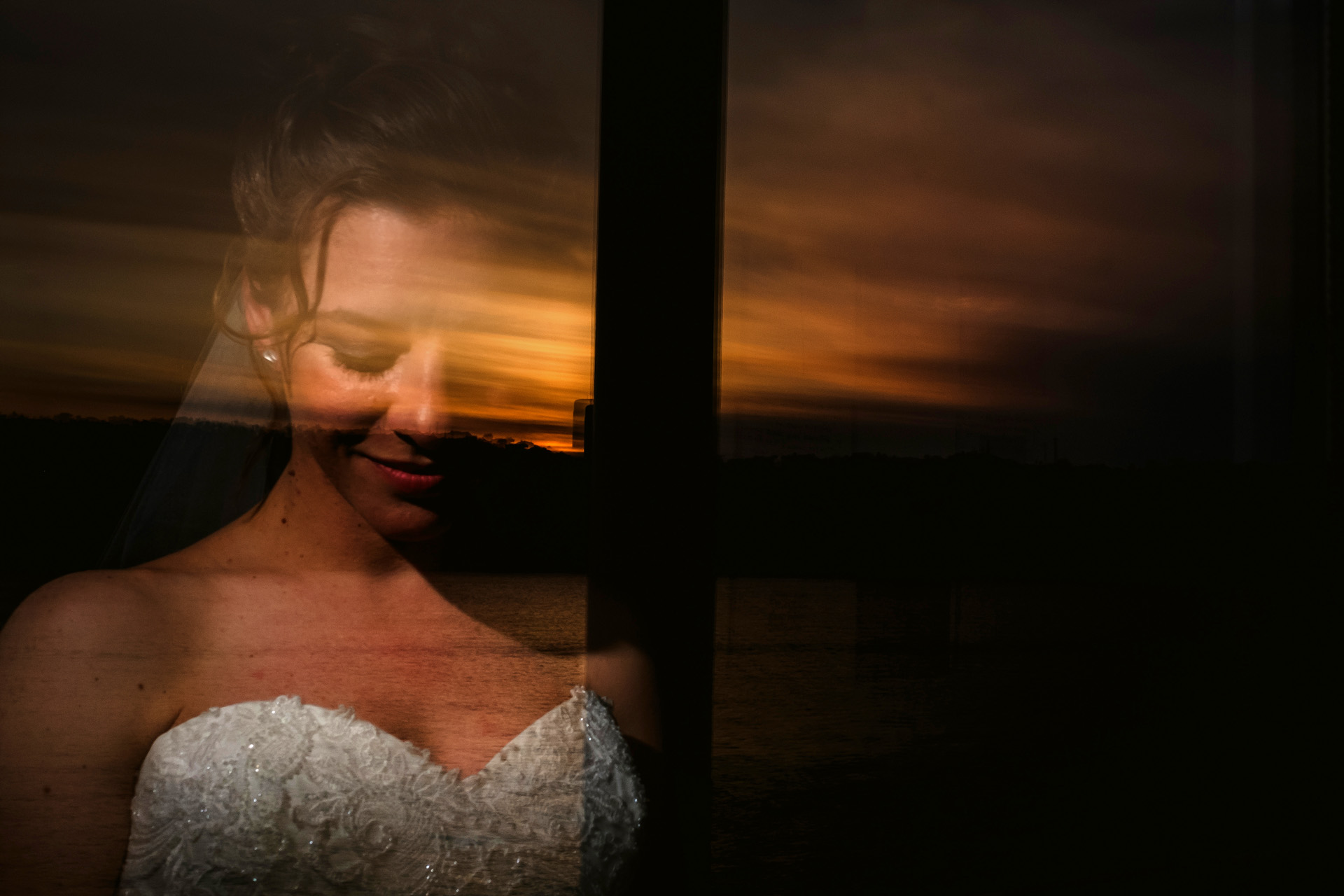 Istanbul, Turkey Wedding Photos | a portrait of the bride reflecting from the hotel window at sunset