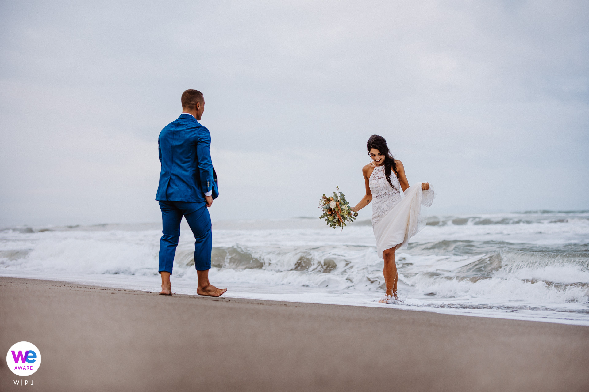 Fiumara Beach Wedding Photo in Italy | The bride is carrying her bouquet and lifting her wedding gown