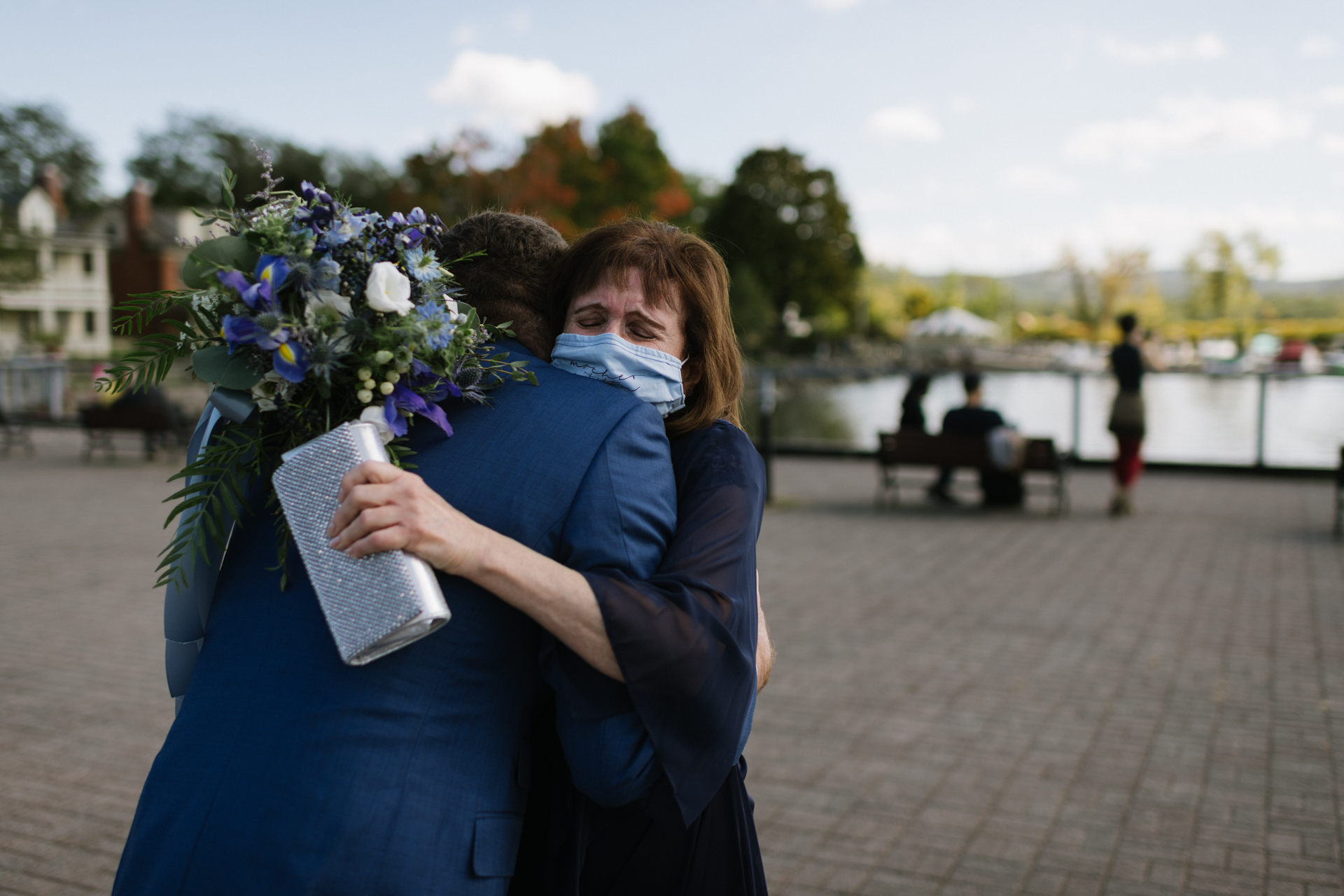 Dockside Park NY Wedding Photography | The mother of the groom hugs her son with emotion