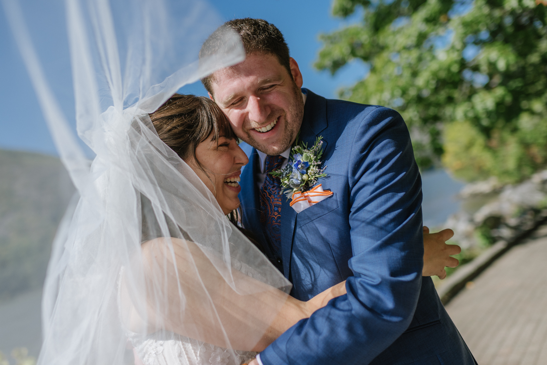 New York Wedding Portrait at Dockside Park, Cold Spring | The newlyweds embrace each other with joy as the bride's veil flies