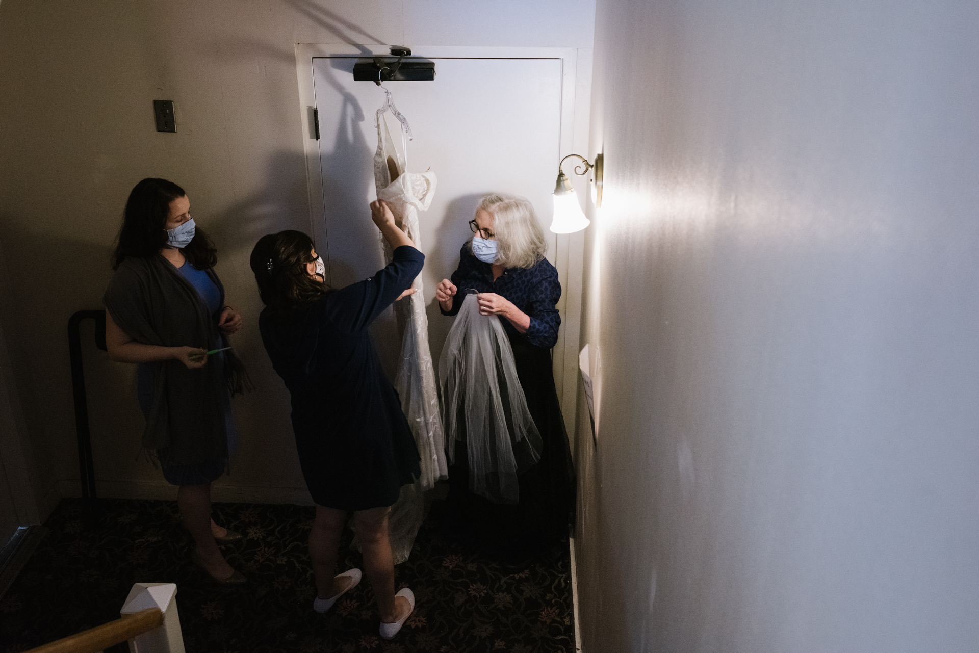 Hudson House River Inn, Cold Spring, New York Wedding Venue Image | The bride takes her dress off a hanger with her mother and a friend beside her