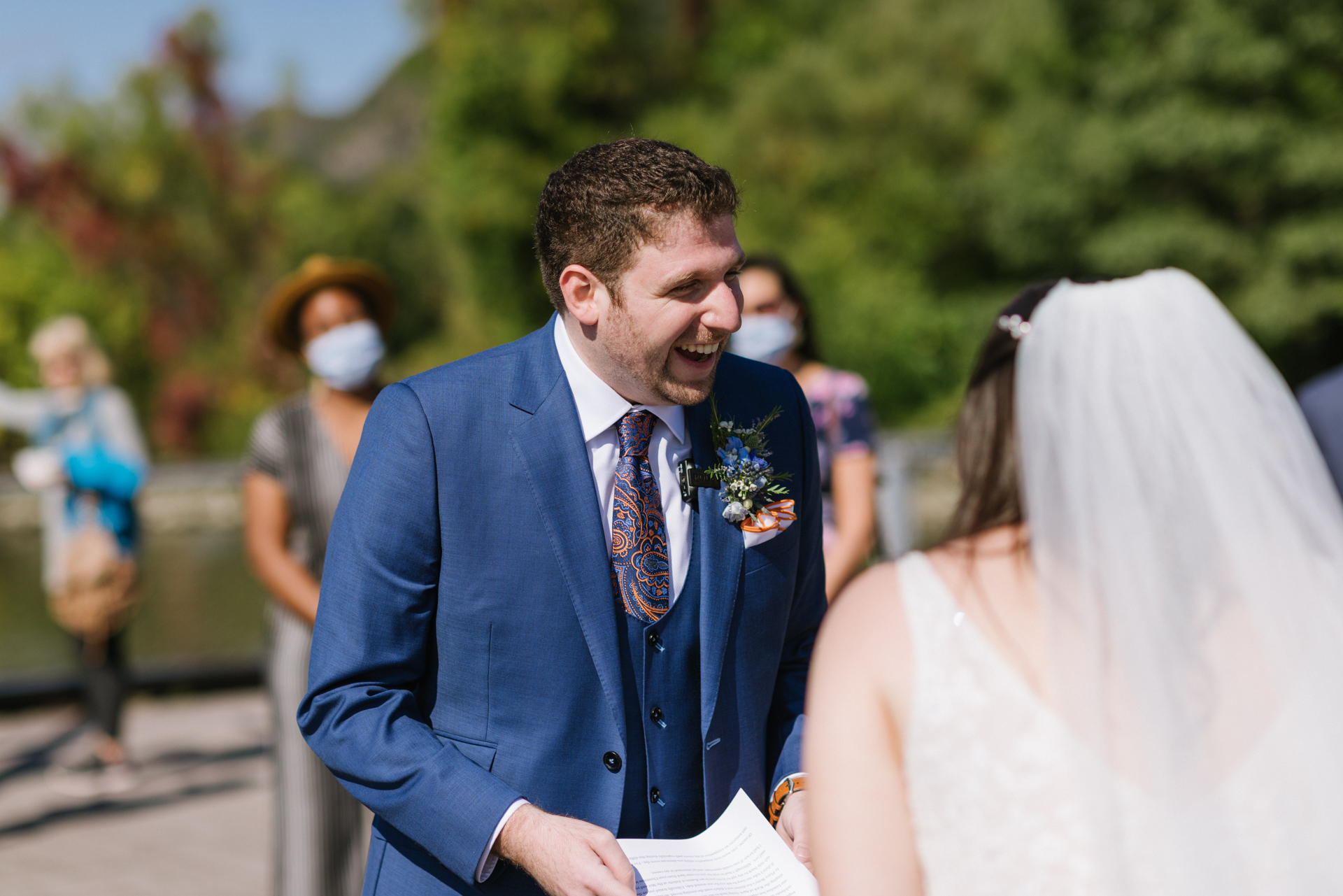 Dockside Park NY Outdoor Wedding Ceremony Picture | The groom laughs joyfully during his wedding ceremony