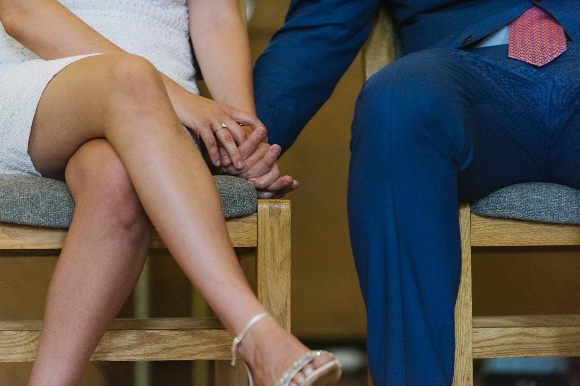 St. Mary of the Angels Chapel Wedding Detail Photo | The couple holds hands while seated
