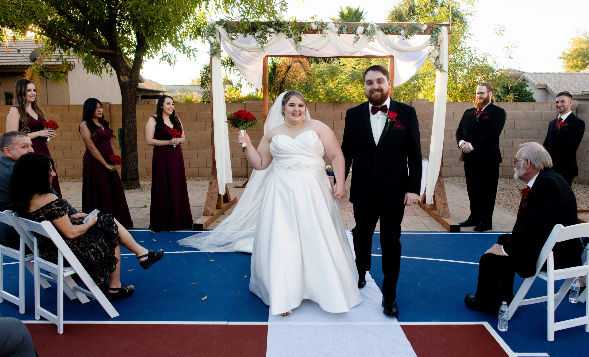 Casual Backyard Wedding Photo in Phoenix, AZ | At the end of their ceremony, the bride and groom hold hands