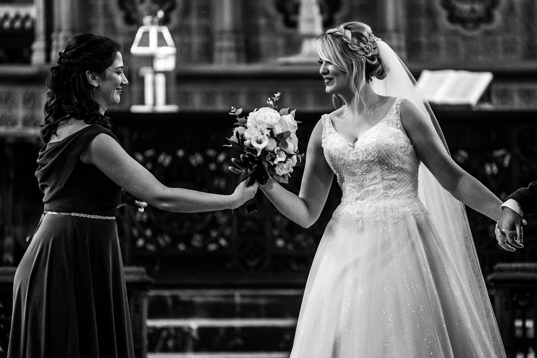 Hull Minster, UK Wedding Image in B&W | A bridesmaid passes the bride the bouquet