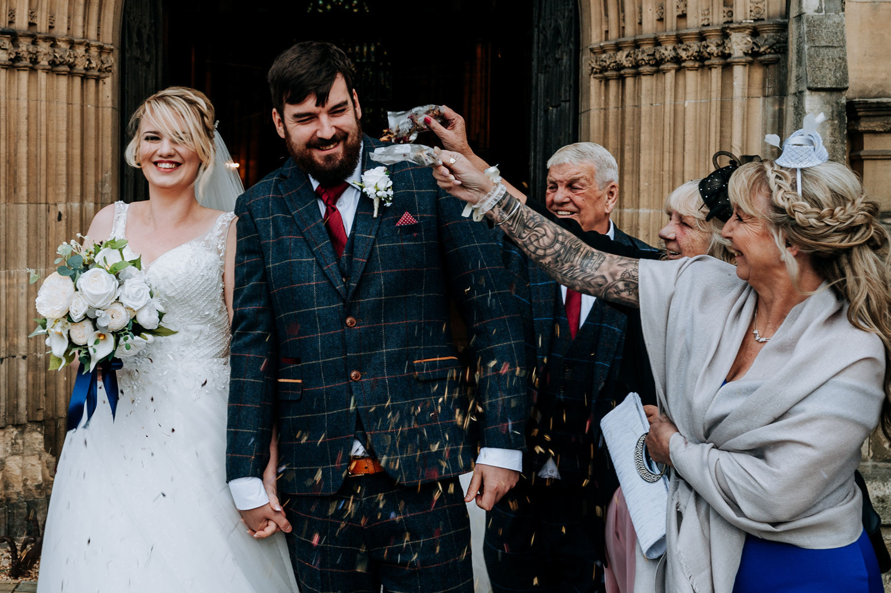 UK, Hull Minster Wedding Image | guests cover the happy couple in confetti