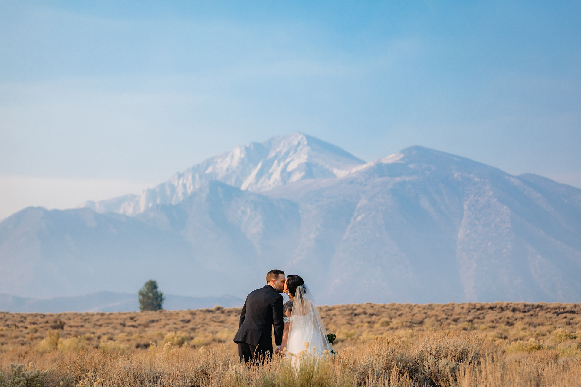 Mammoth Lake Wedding Day Couple Portraits | The bride and groom kiss as they pose for a portrait