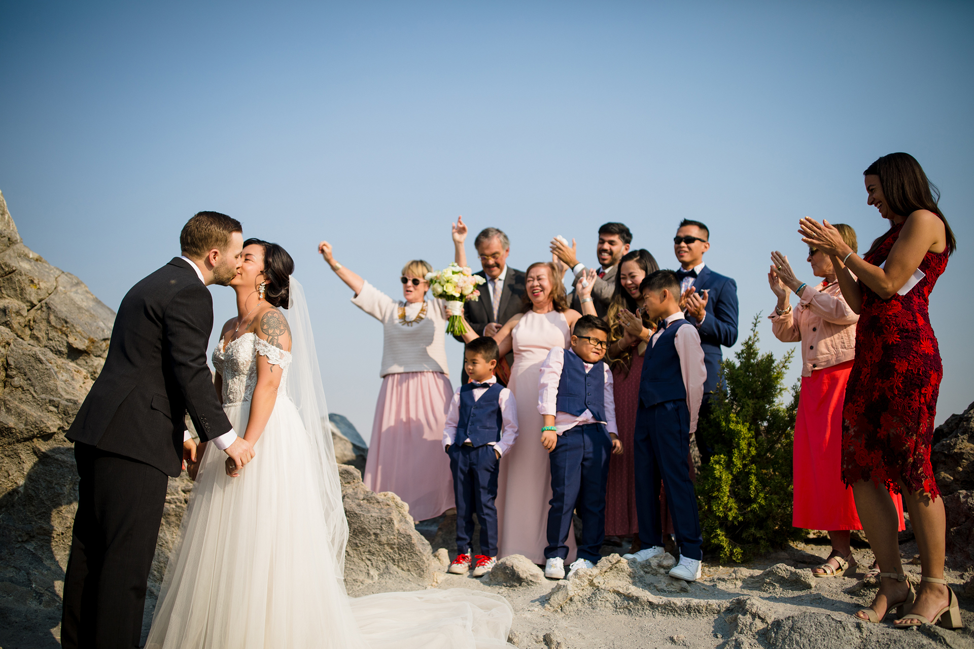 Mammoth Lake Outdoor Wedding Photo | The bride and groom sneak in a kiss as their family members and friends cheer
