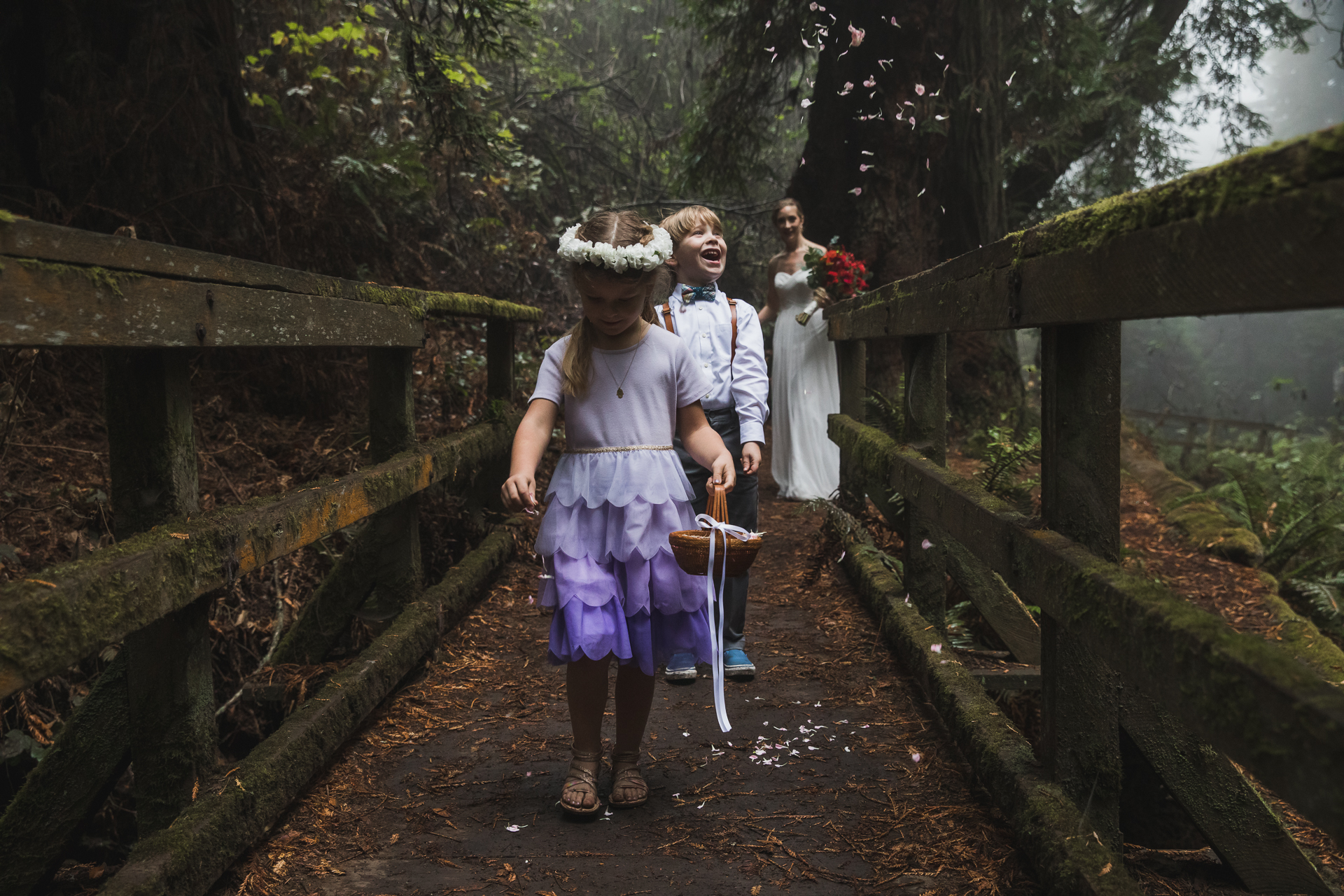 Redwood Forest - Stinson Beach CA Wedding Photos | The flower girl and ring bearer walk across an old mossy wooden bridge