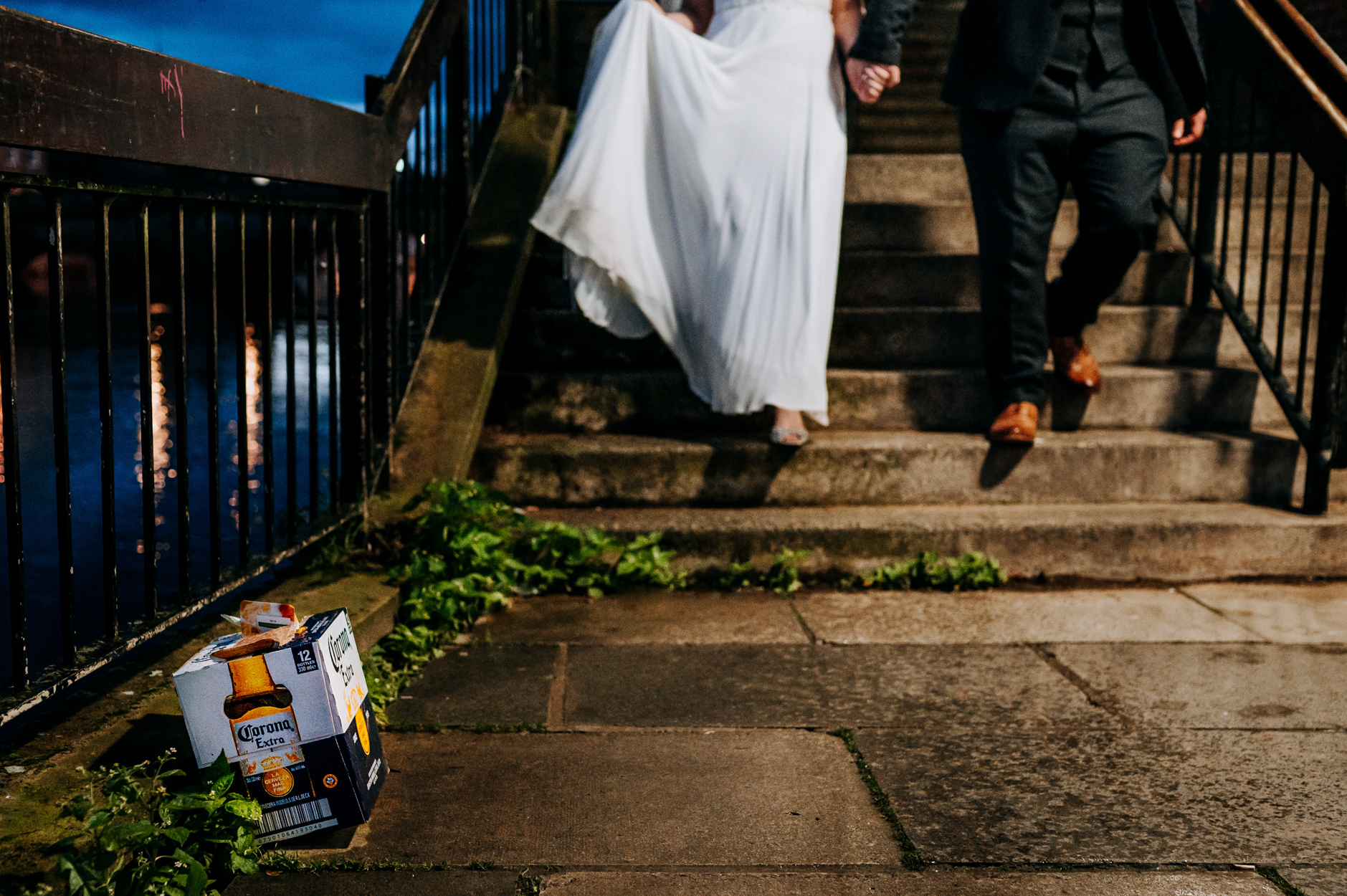 Wedding Photographers of York, UK | The couple leave their reception and walk past a dumped, empty box of Corona beer
