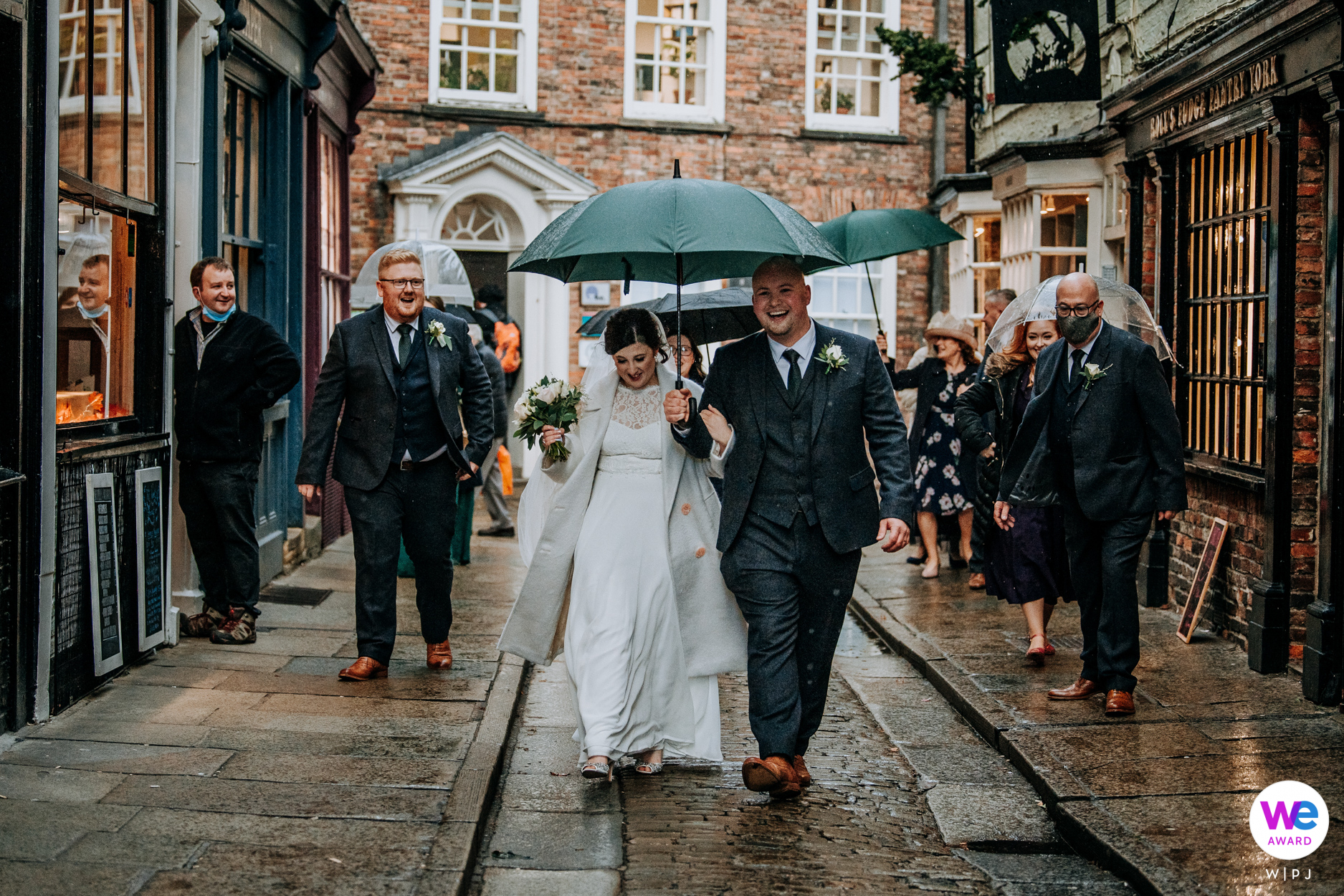 The Shambles, North Yorkshire, UK Wedding Photo | the bride and groom and their wedding guests walk along the famous 'shambles' in York