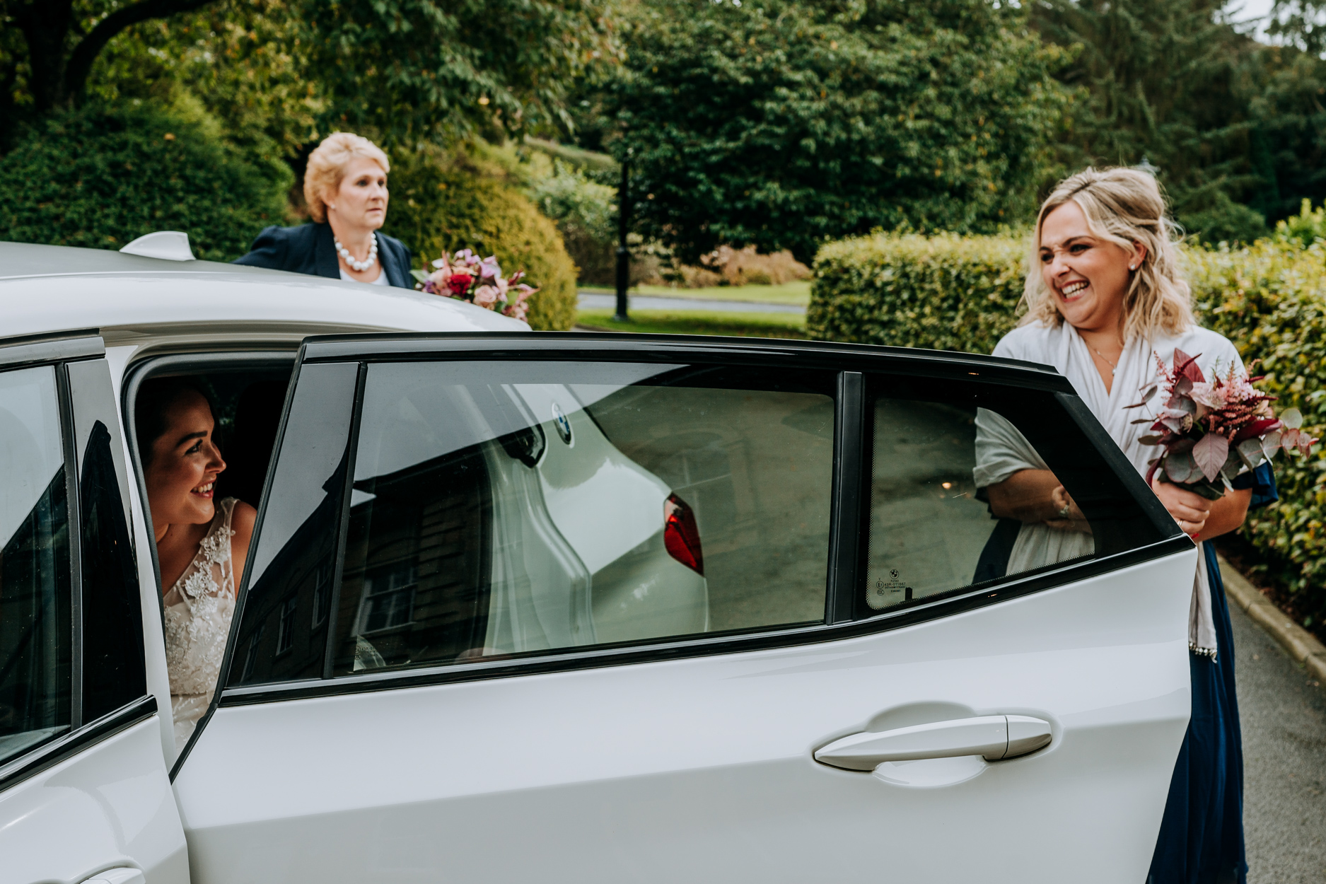Hackness Grange Country House Hotel Wedding Pics | The bridesmaid holds open the car door