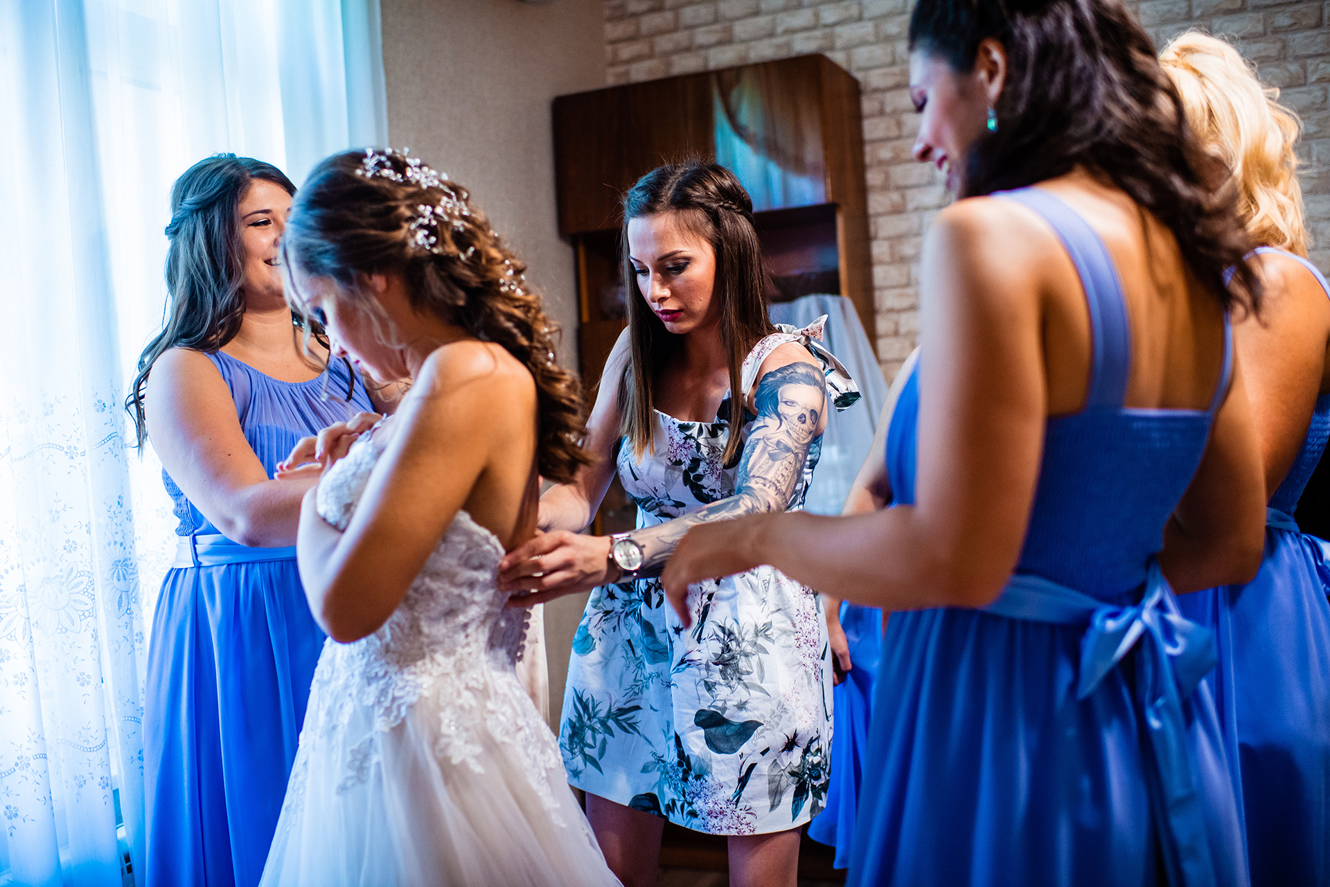 Ruse Wedding Photographer | The bridesmaids surround the bride while helping her with her gown