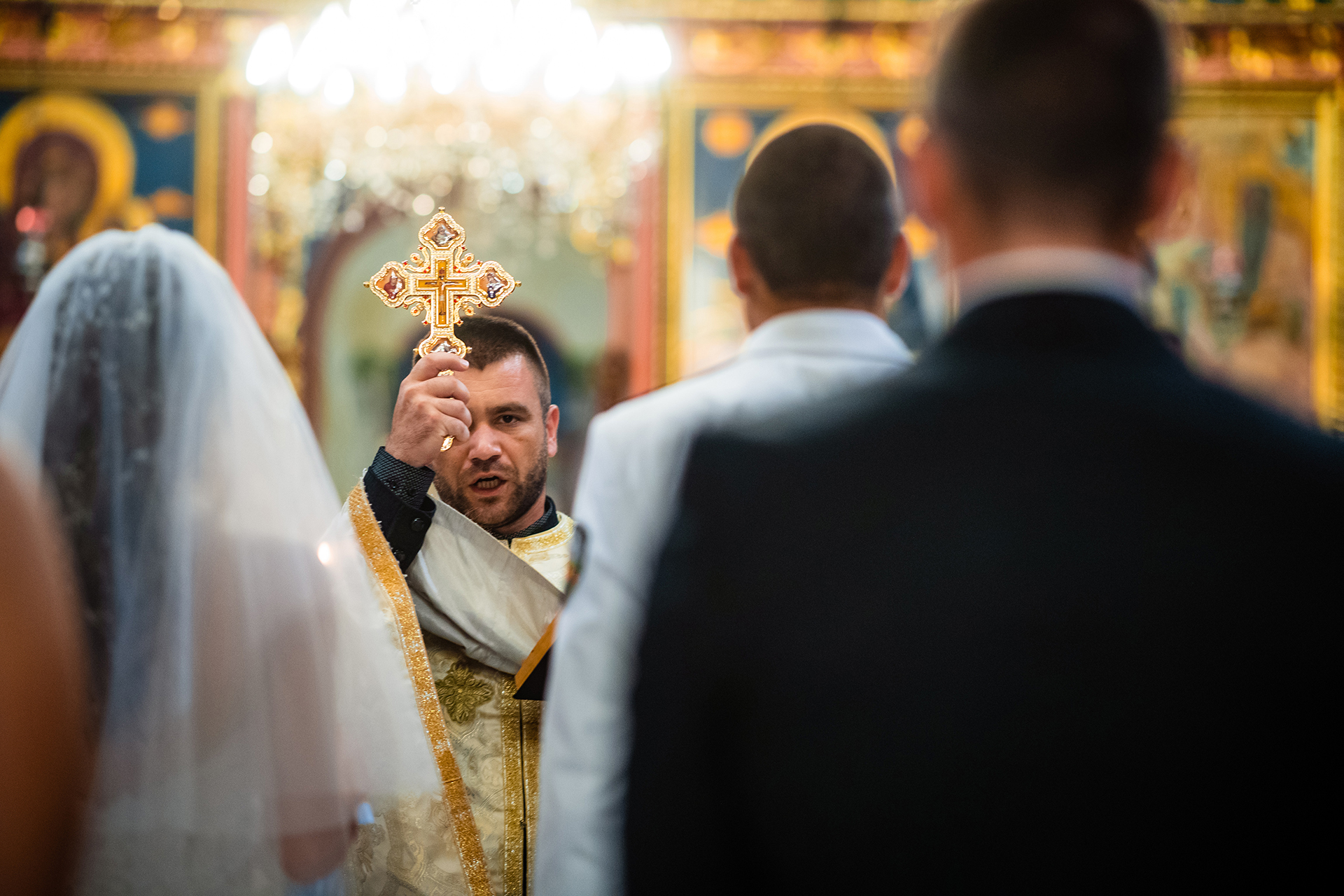 Ruse Wedding Photography from Holy Trinity Cathedral | The priest holds up a cross, and the couple recite their vows before God