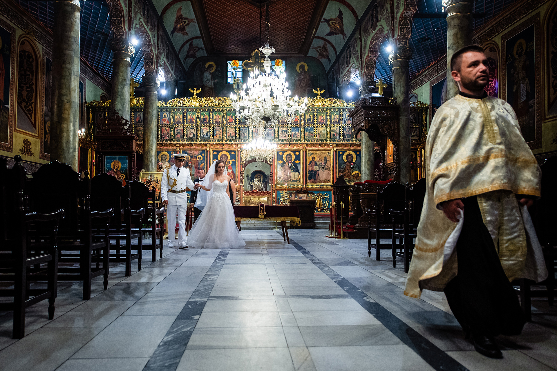 Holy Trinity Cathedral, Ruse Wedding Photographer | The groom holds the hand of his bride