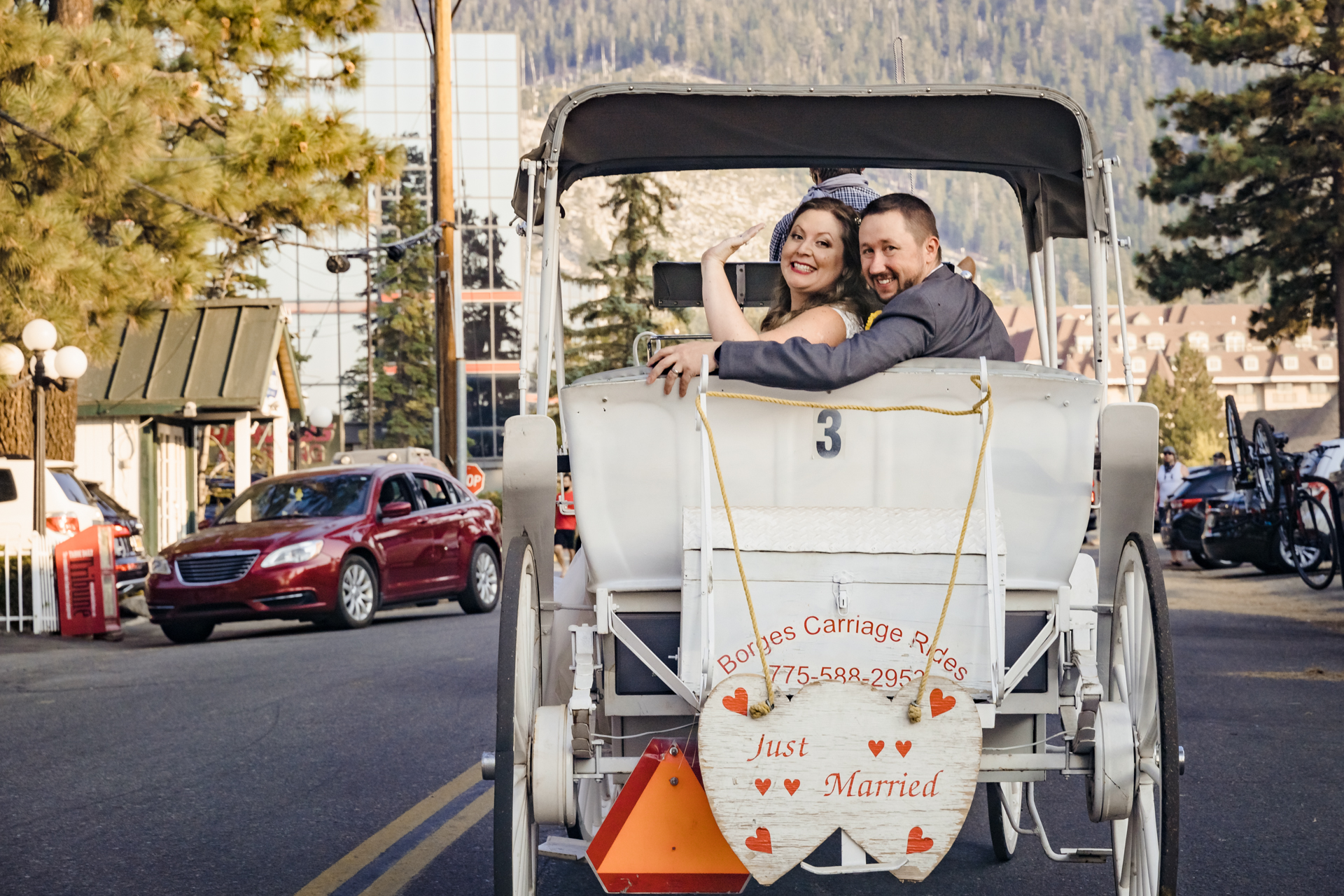 Lakeside Beach Wedding Venue Pic - South Lake Tahoe | The newlyweds wave from their horse-drawn carriage