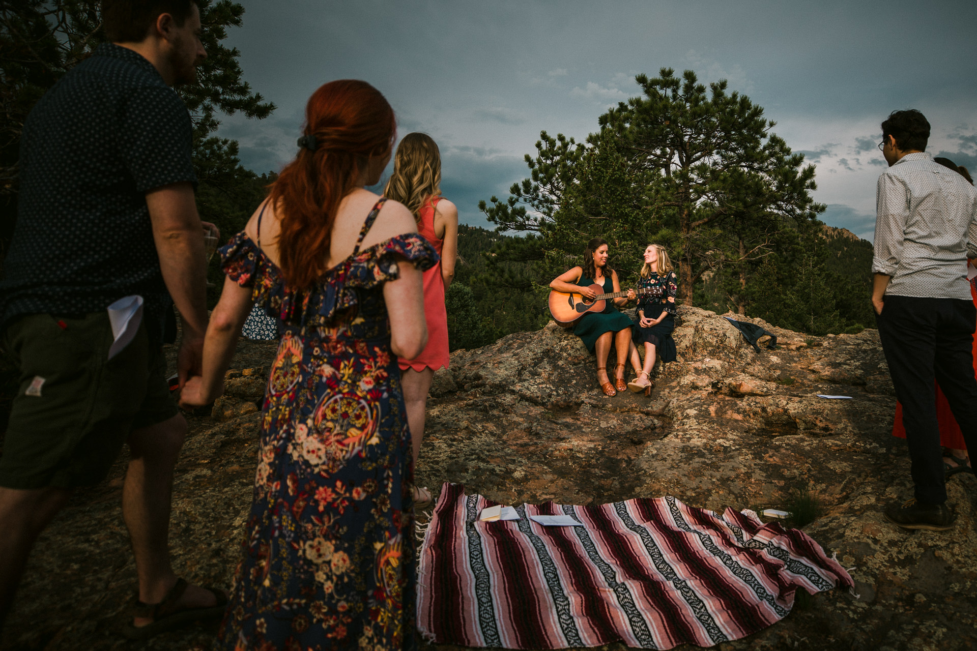 Colorado Mountains Wedding Photo - performing a song with a guitar outside on the rocks