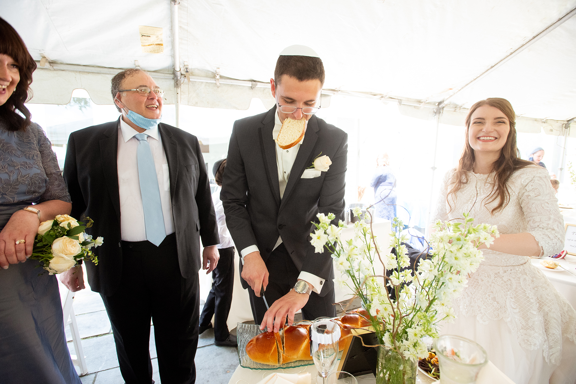 Pittsburgh, PA Wedding Image | The groom is using his mouth to hold on to a slice of challah