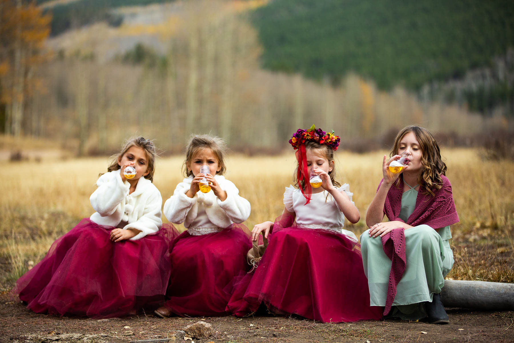 Photos from a Kenosha Pass Adventure Wedding | The 4 flower girls gather together on a log to enjoy apple juice