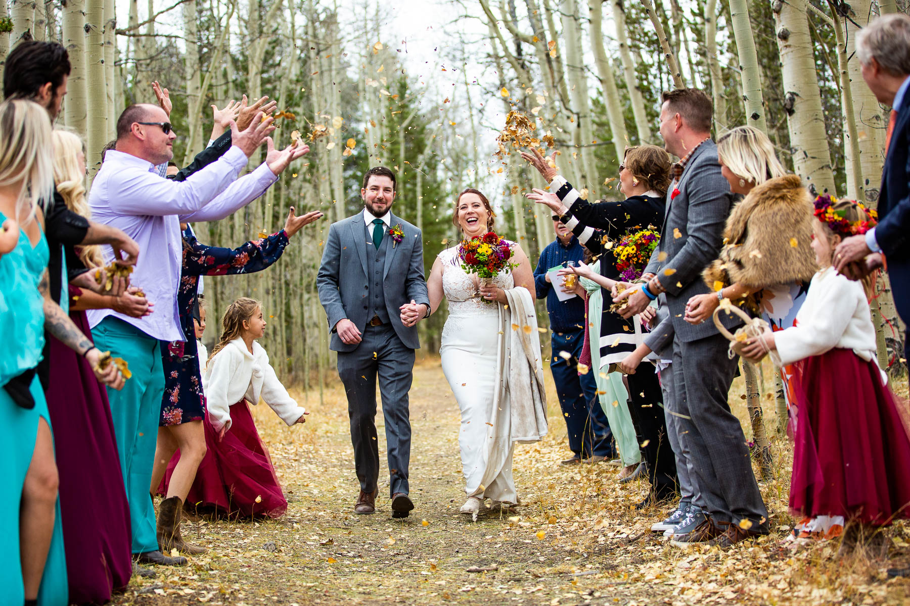 Colorado Mountain Wedding Photo Session | the couple's friends and family members scooped up fallen aspen leaves and tossed them