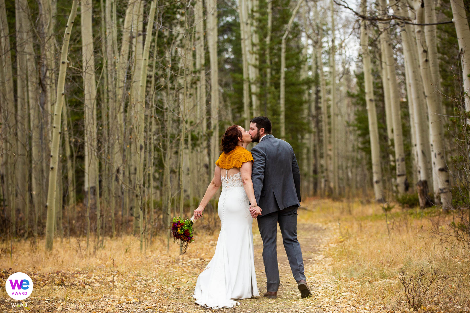 Kenosha Pass, Colorado Wedding Photography | The newlyweds sneak a kiss while walking through the forest