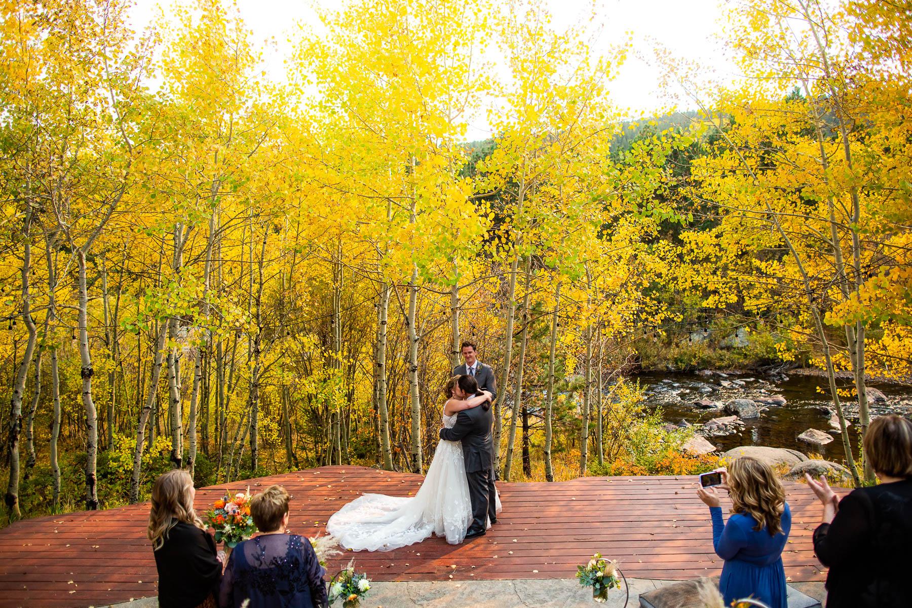 Foto del sito per la cerimonia all'aperto di Wild Basin Lodge | Si strinsero l'un l'altro in un grande abbraccio per il loro primo bacio