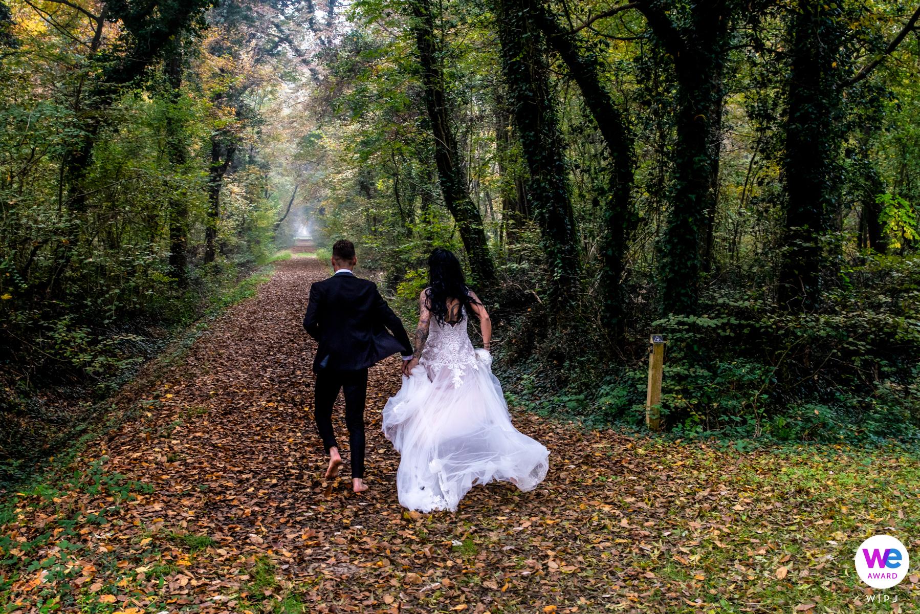 Hochzeitsfoto von Agriturismo Corte Barco | Hand in Hand laufen sie barfuß zum Lichtpunkt am Ende eines langen Korridors, der von Bäumen gebildet wird